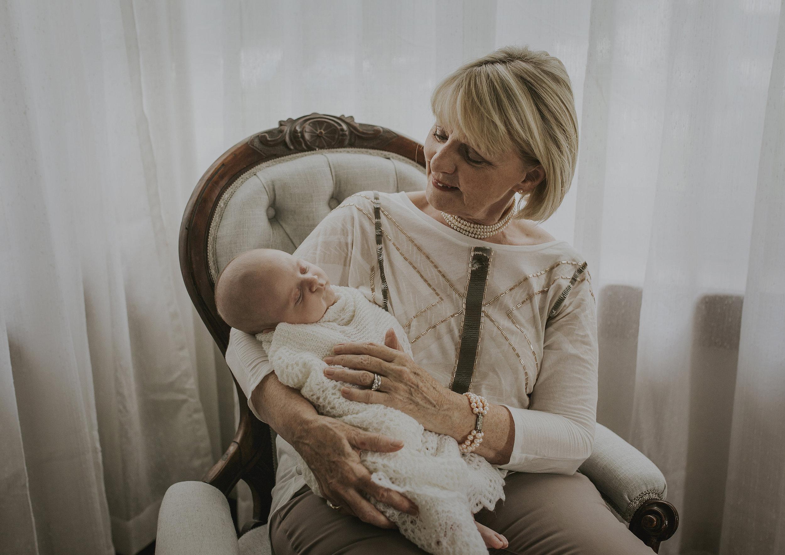Grandmother holding her newborn baby grandson