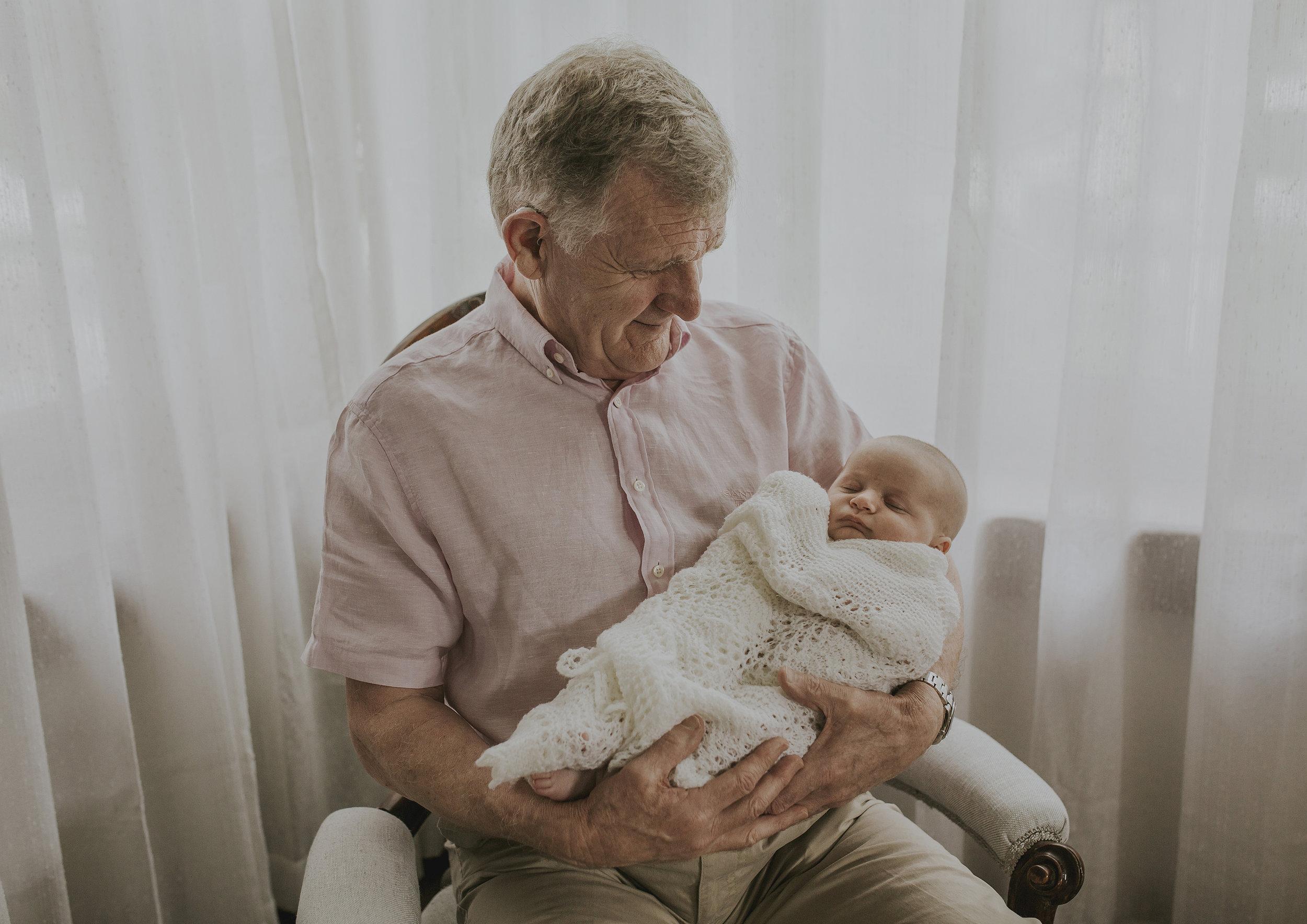 Grandfather holding his newborn grandson