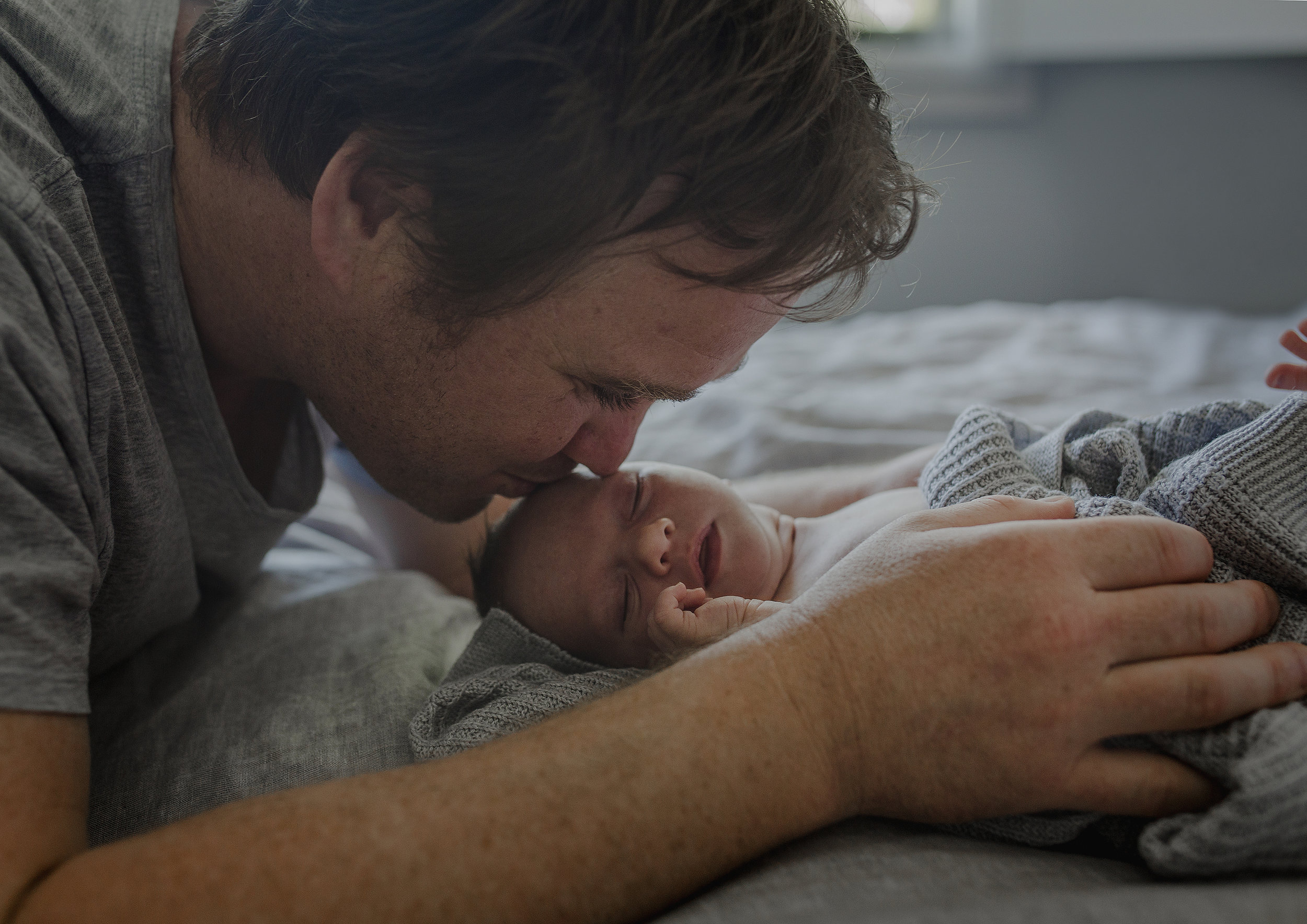 New Dad kissing his newborn baby son