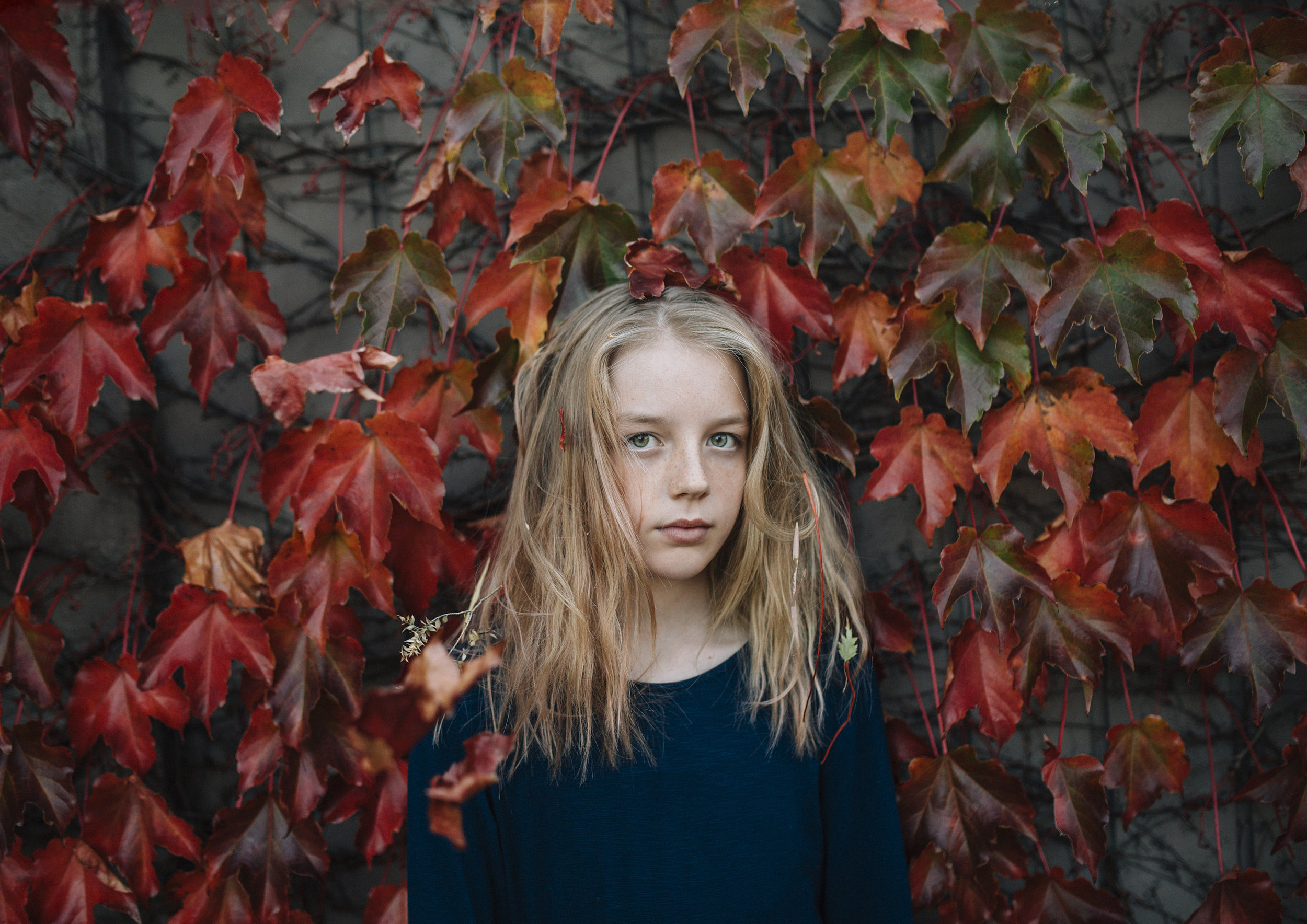 Tween girl posing in front of a wall of Autumn leaves