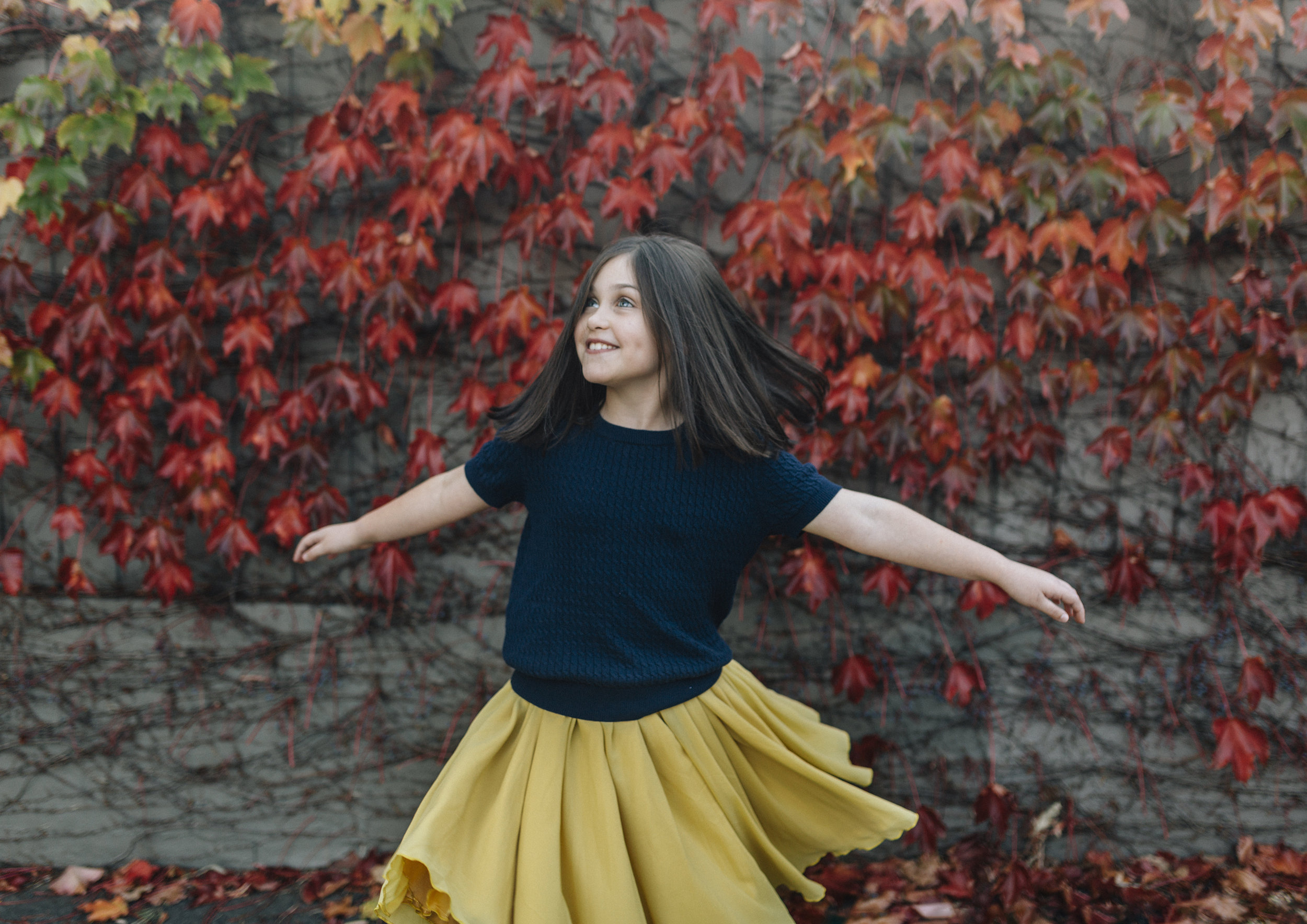 Young tween girl dancing amongst the Autumn leaves