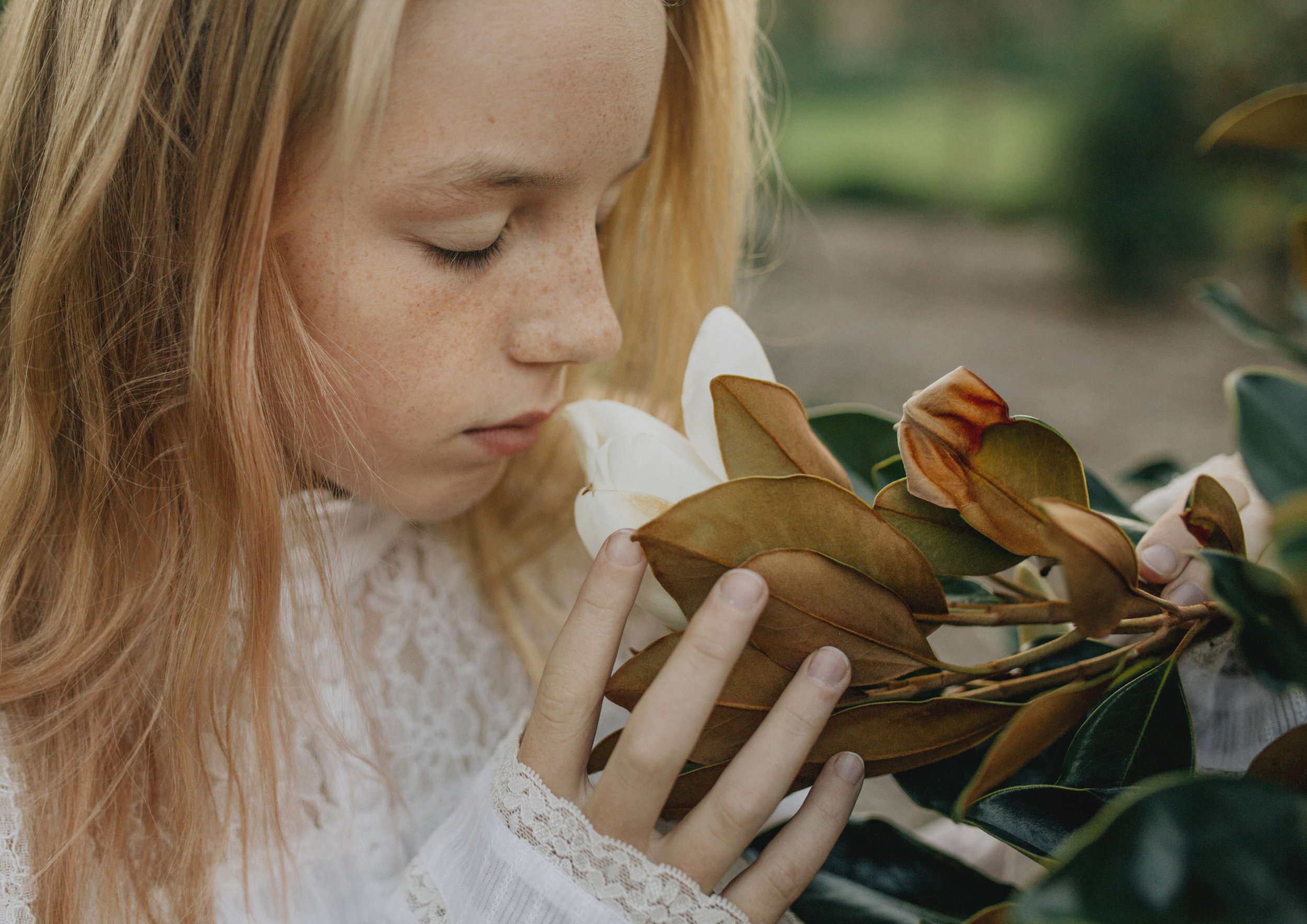Tween girl smelling Magnolia flower