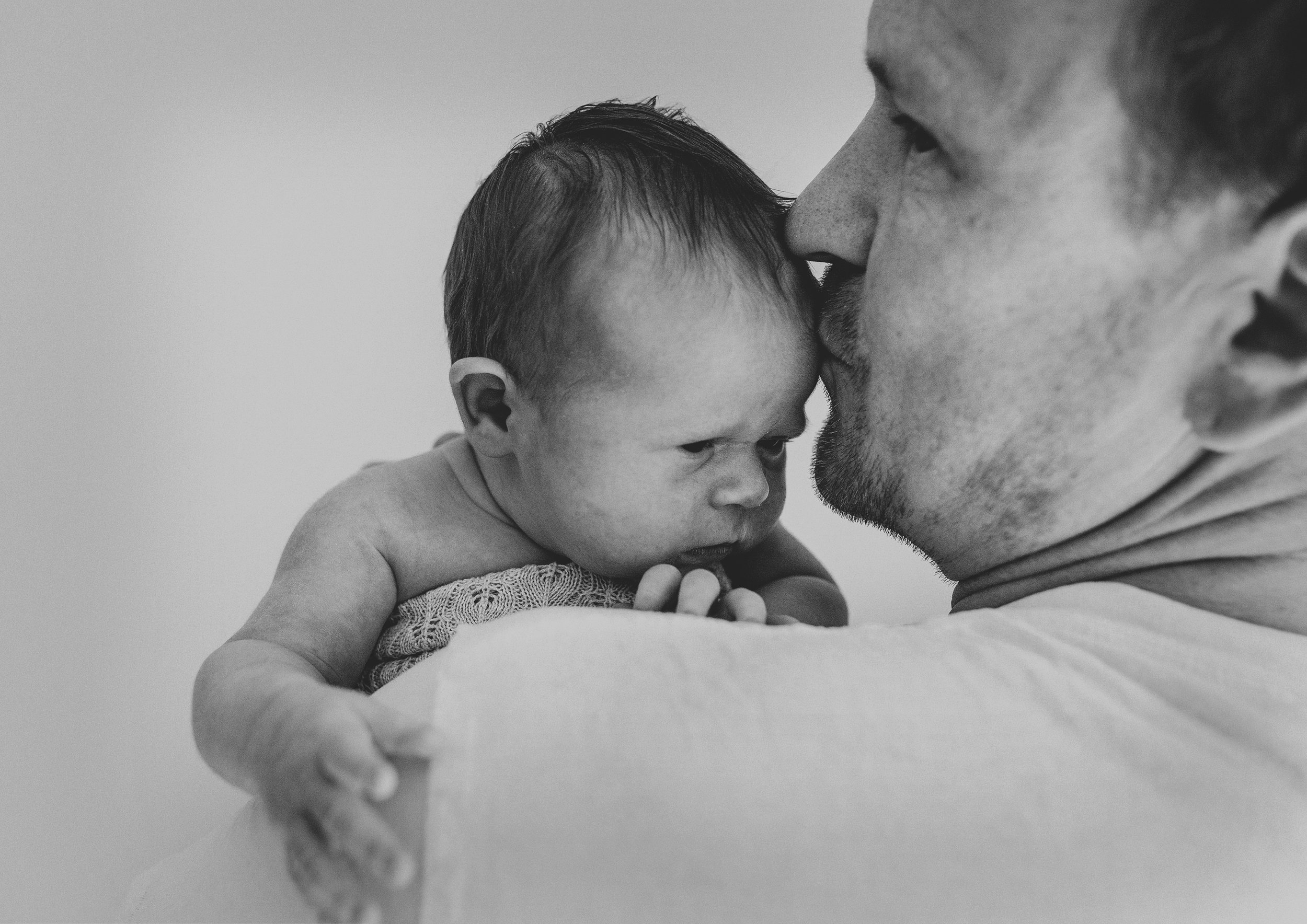 Dad kissing his newborn baby son