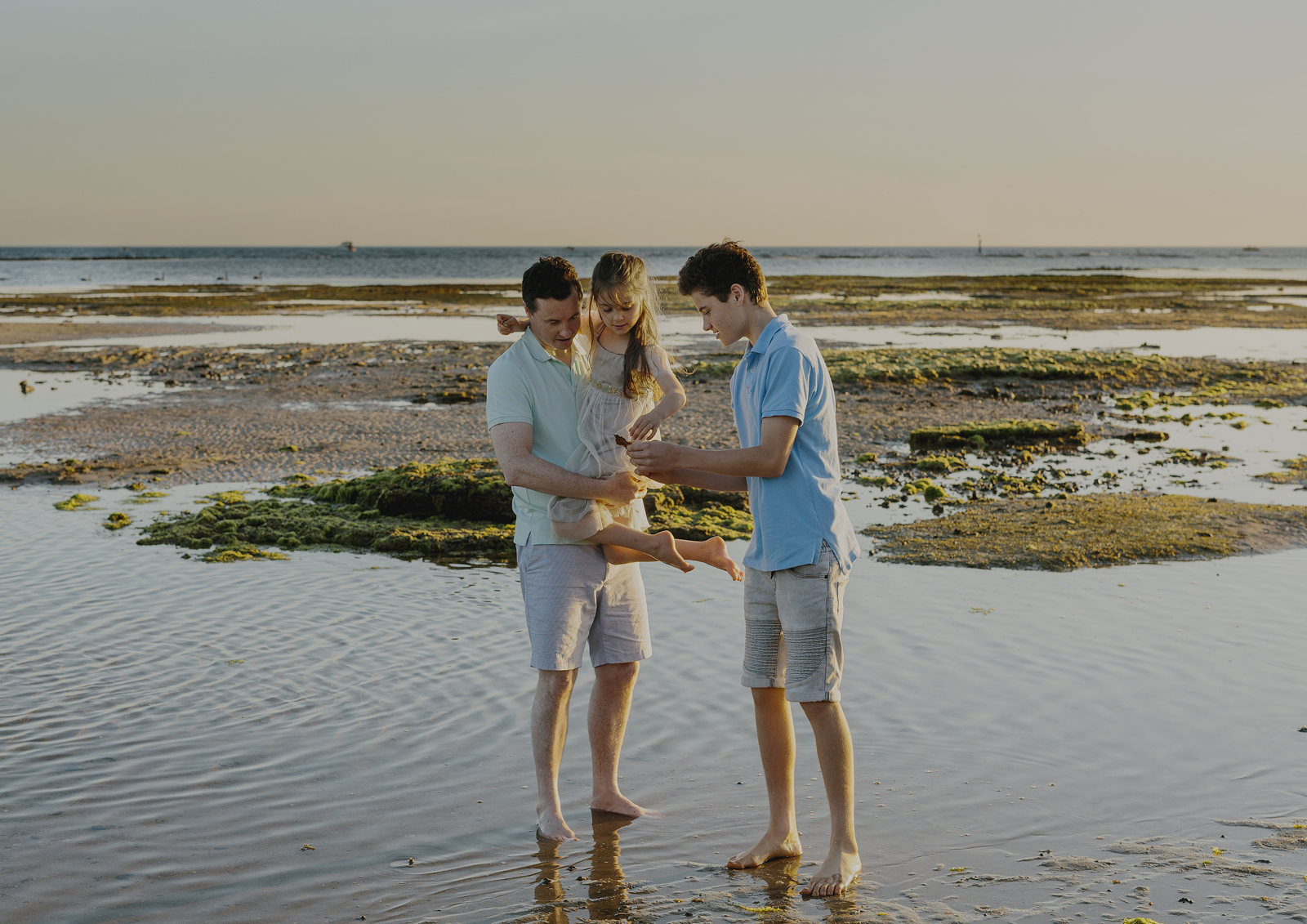 Family searching the rock pools at the local beach
