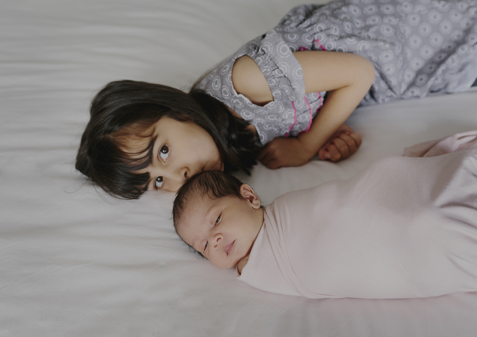 Big sister besotted with her newborn baby sister