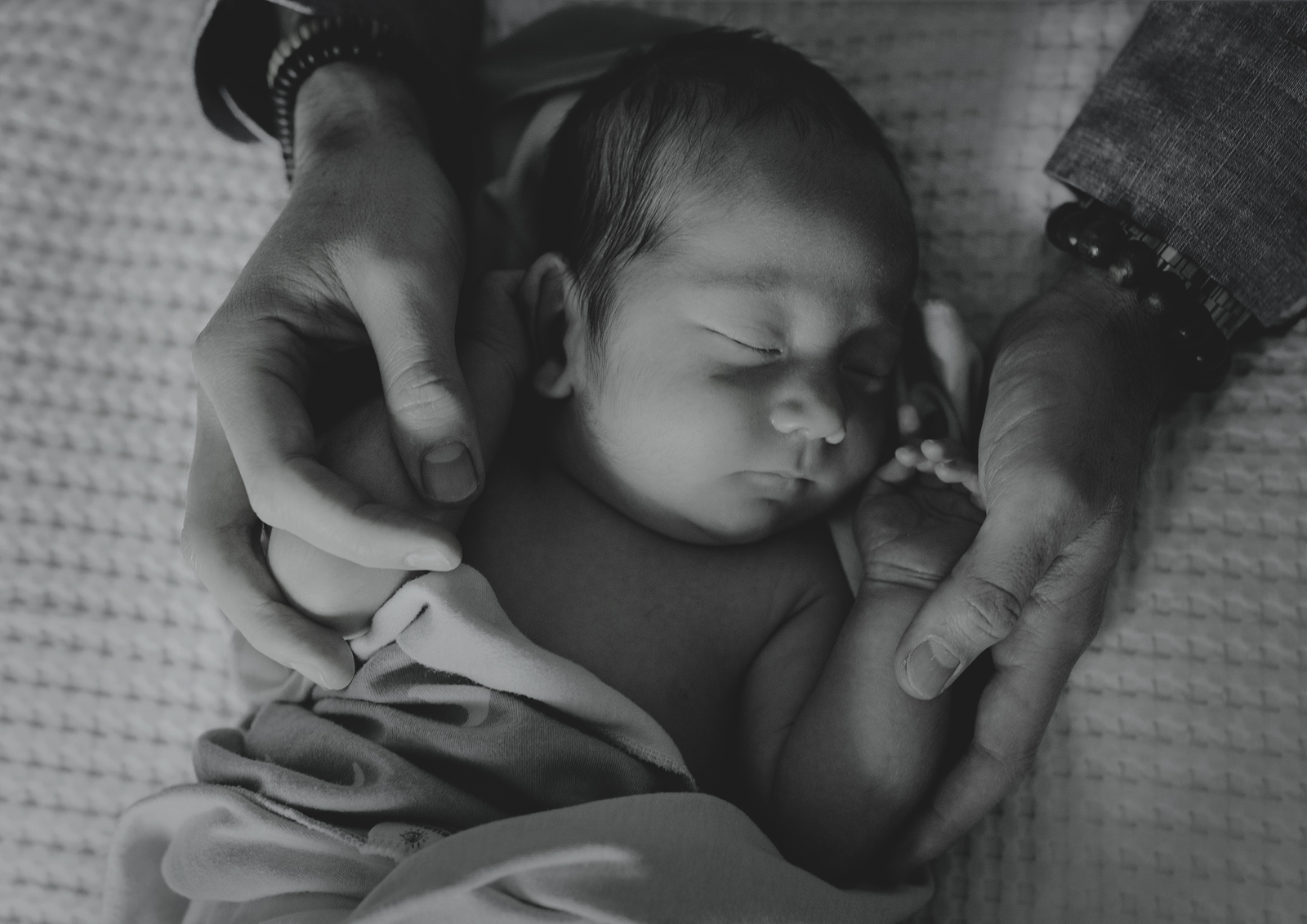Newborn baby boy protected in his father's hands