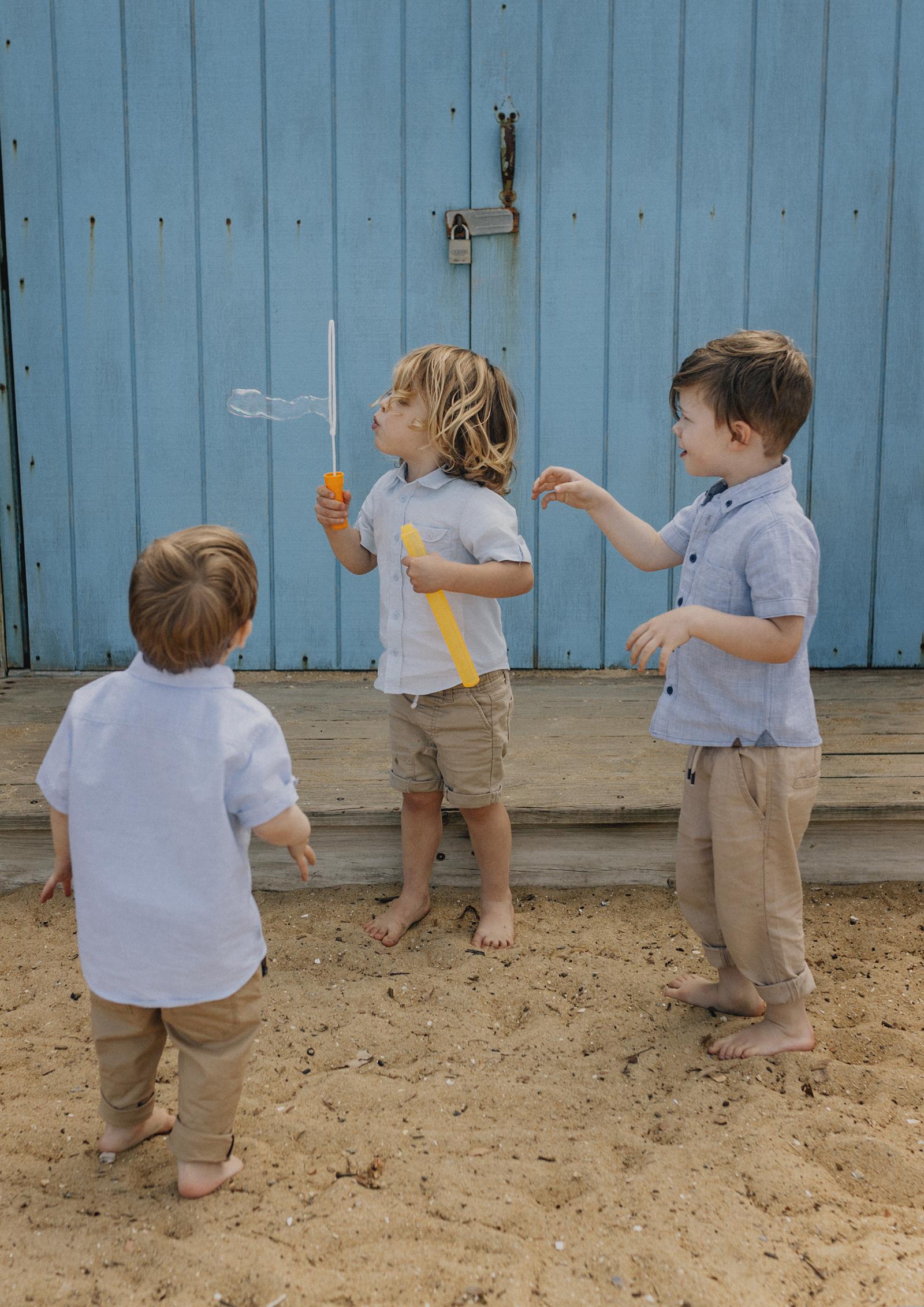 Cousins having fun blowing bubbles at the beach