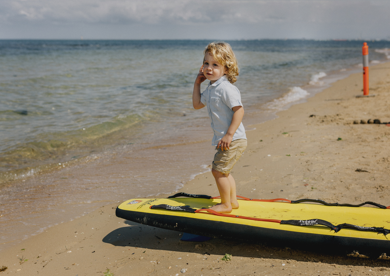 Child trying out a surf board down at the beach