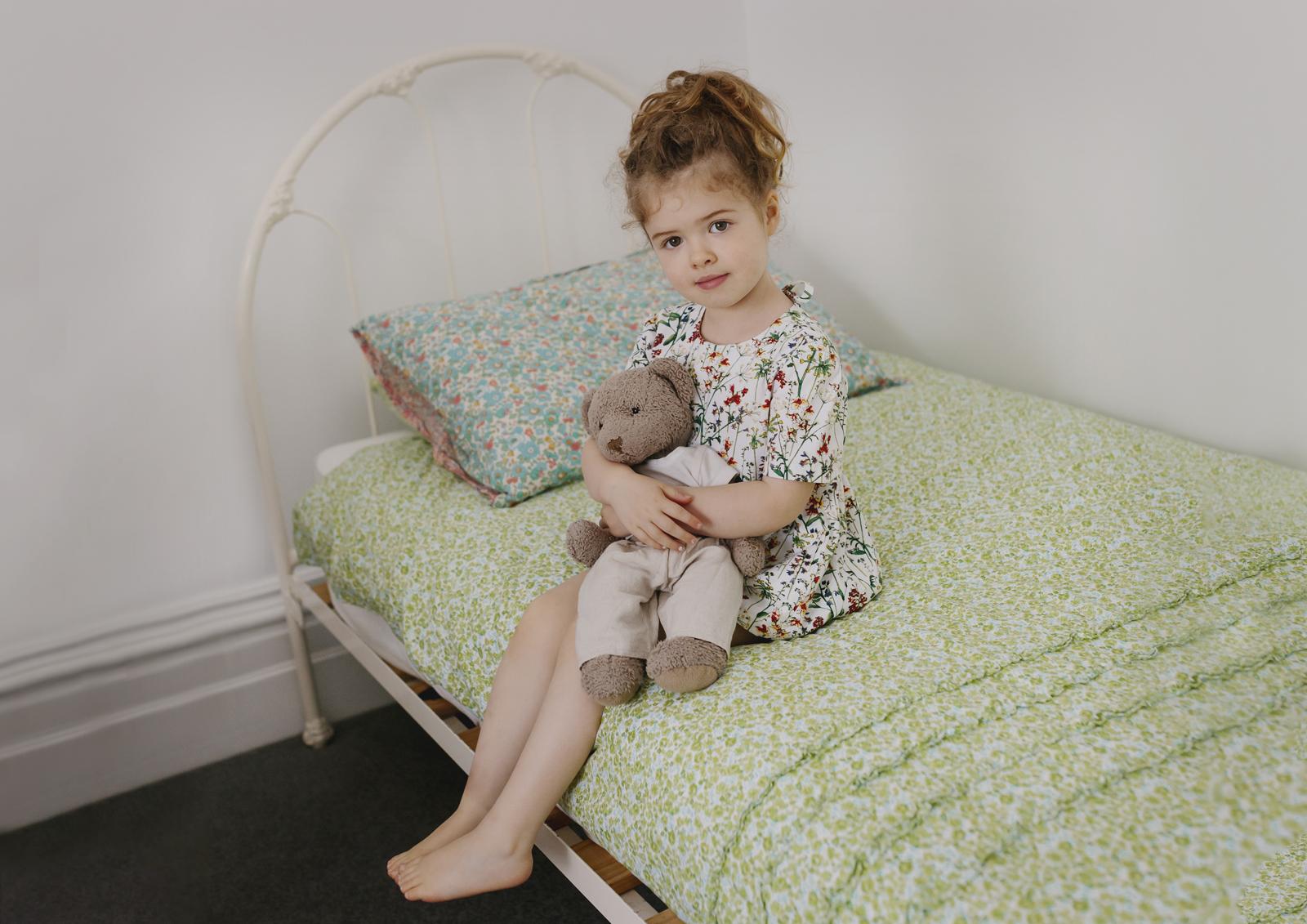 Child sitting on her vintage bed