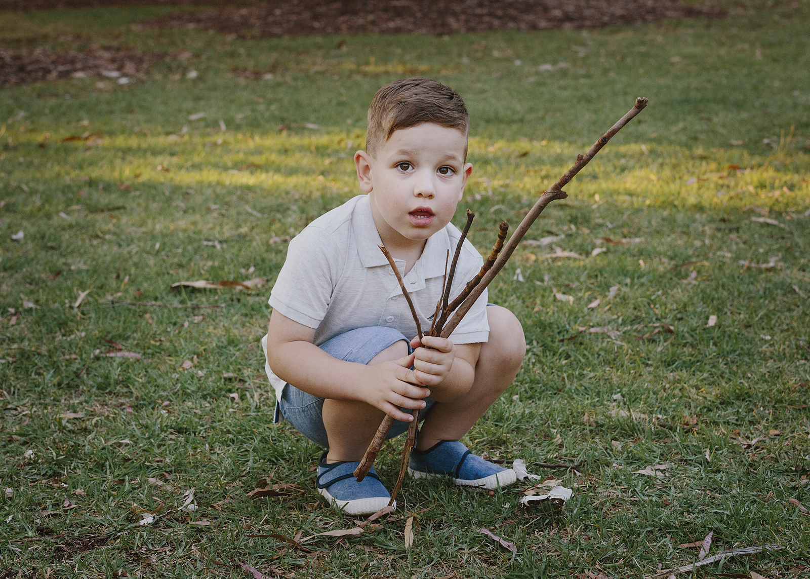 Child playing with twigs at the park