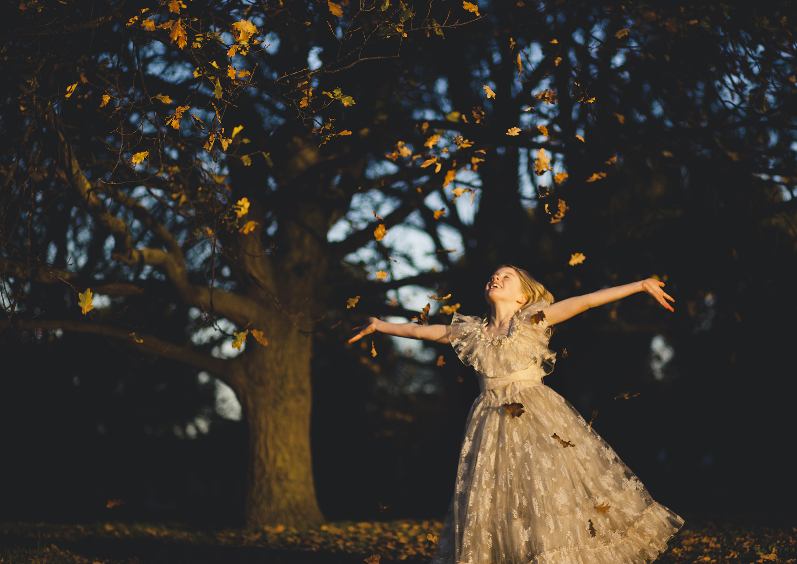 Tween girl throwing Autumn leaves in the air