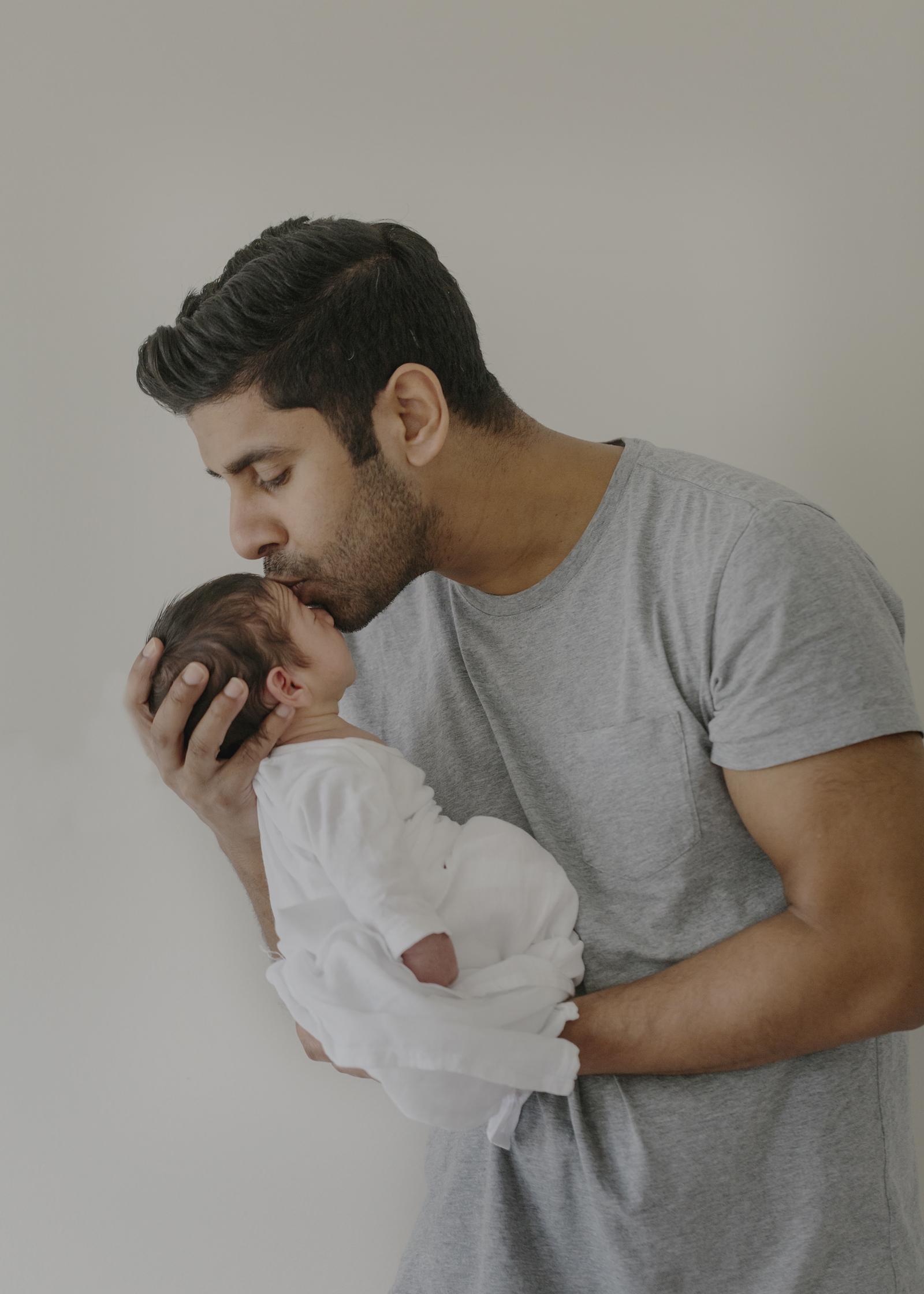 New Dad kissing his newborn son