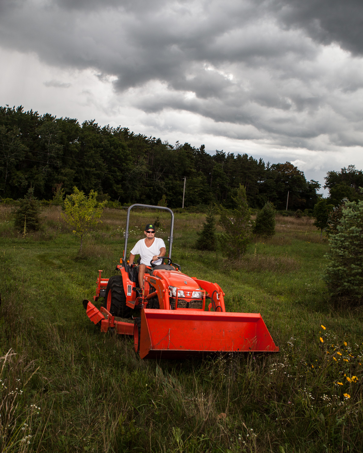 Christian mowing the grass at our farm with the tractor. Christian loves big machines.