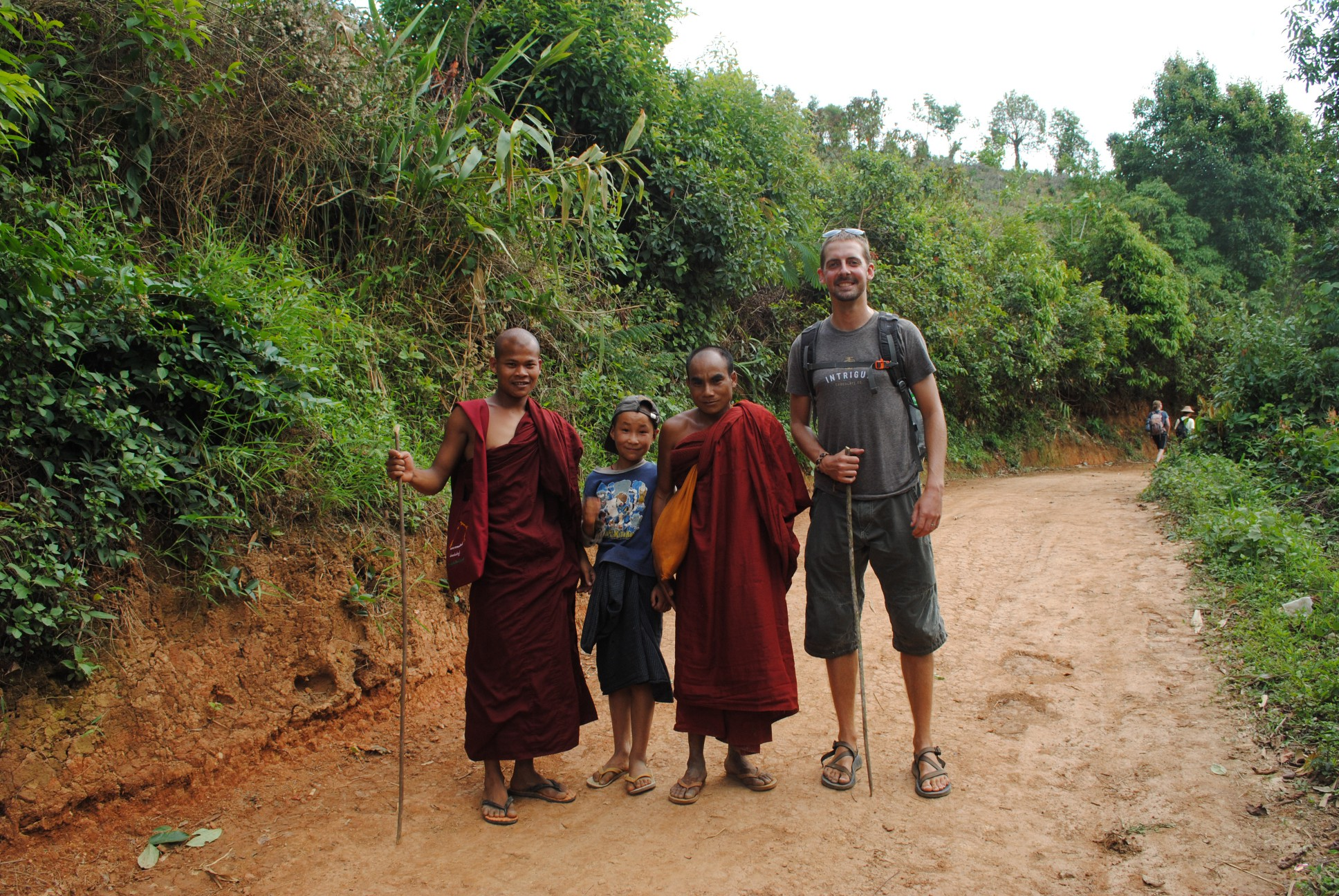 Jason with two monks and a local kid.
