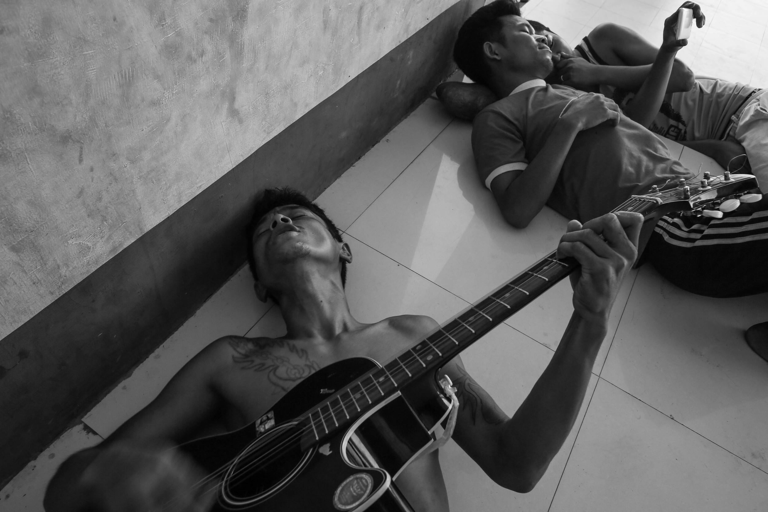 Brang San Aung, left, in his thirties, plays the guitar while singing with friends at the Aung Mintha rehab camp. Music seems to be the best way to pass the time in rehab. Brang San Aung is HIV positive and used heroin for seven years. He died from unknown causes months after this photo was taken.
