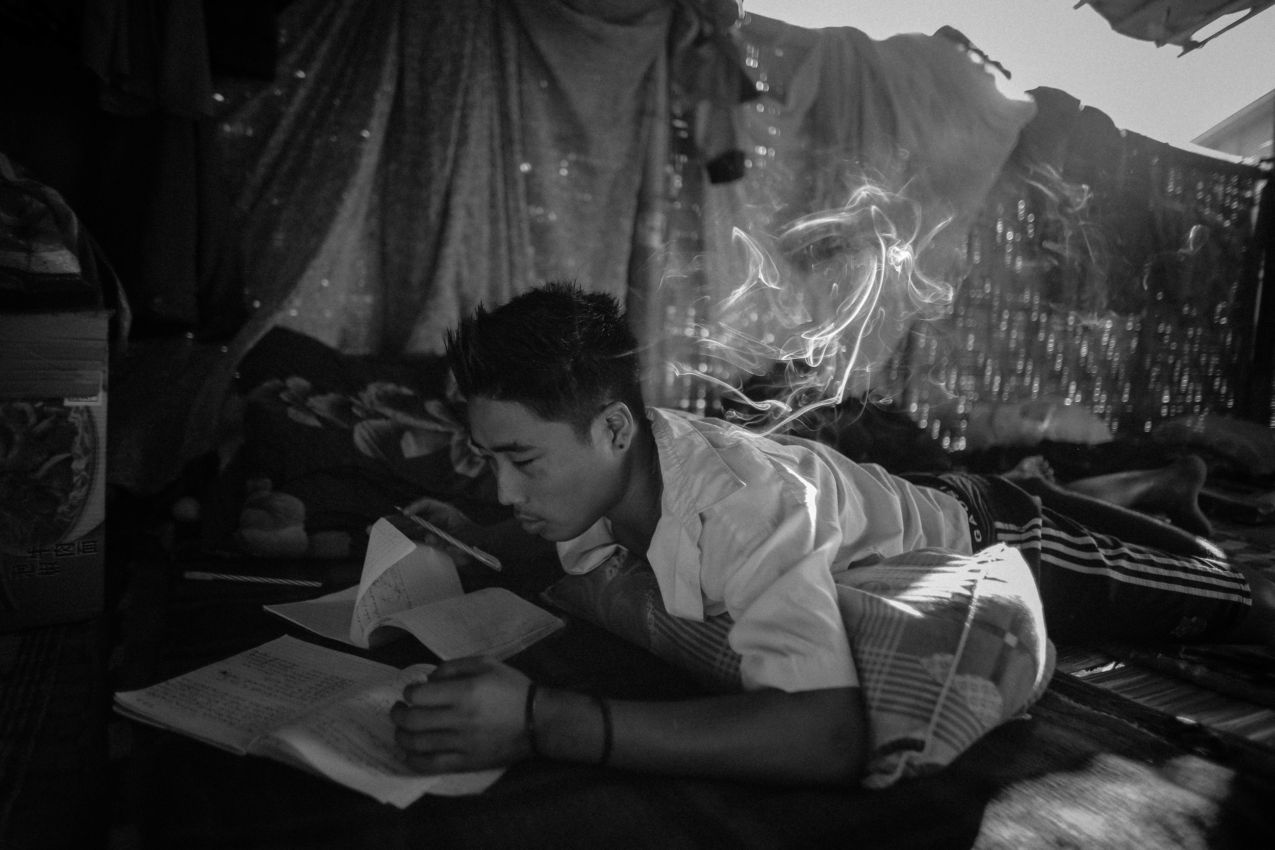 """Moe Kyaw Thu, 22, does his bible study homework in the Aung Mintha dormitories. He was a gold miner and an addict for three years. He left the rehab center only three days before his """"graduation."""""""