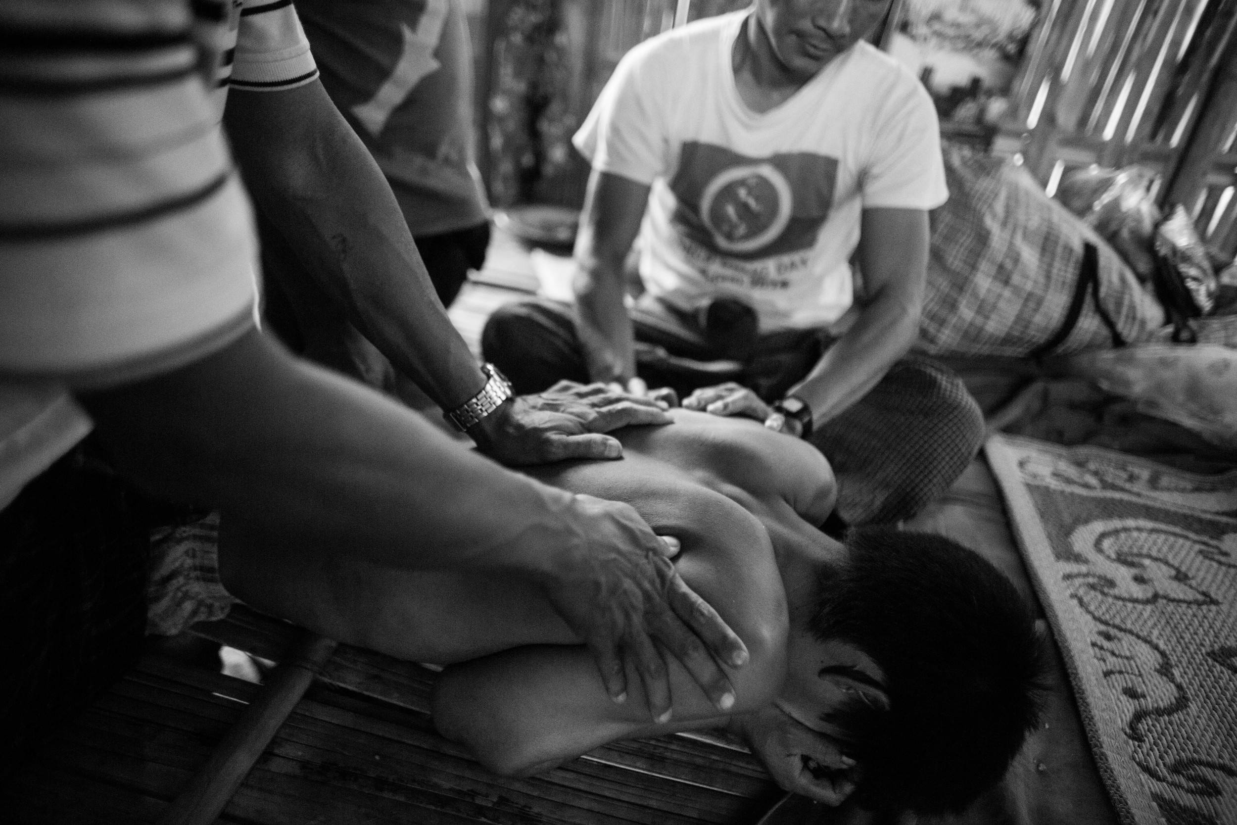 YCC staff members massage Hkun Aung, 34 while suffersthrough withdrawal pains. Hkun Aung has been an addict for 16 years and this is his third day in rehab.