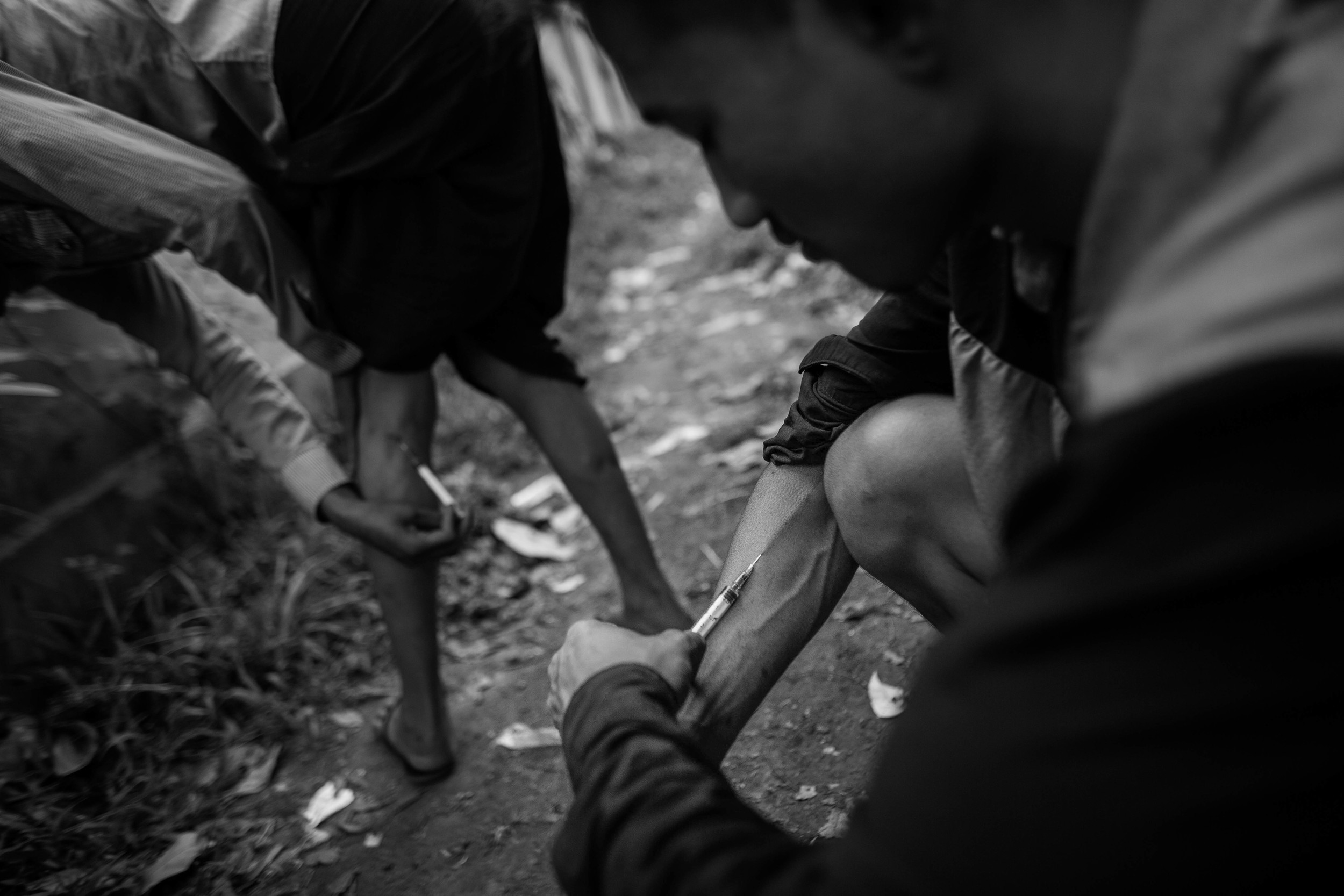 Two addicts shoot up in an alley in Myitkyina, the capital of Kachin State, Myanmar. They say they have to shoot up five to six times a day. It costs between $5 and $10 per hit.