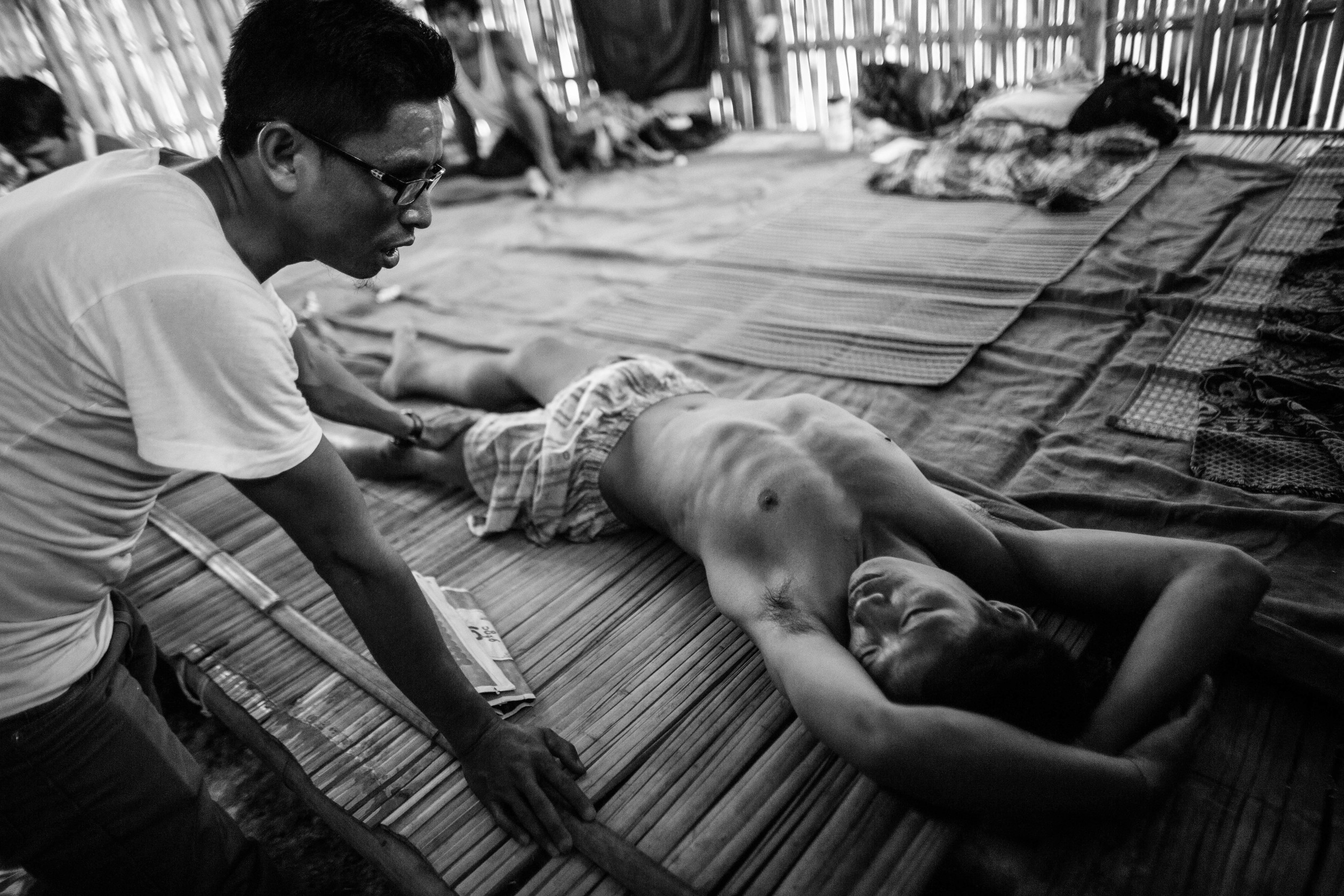 """Hkaw Zung, left, a YCC rehab center staff member talks toHkun Aung, 34. """"Hkun Aung"""" has been an addict for 16 years. This is his third day in rehab and he'sin severe pain. """"I can't do this anymore,"""" he tells the staff. Hkaw Zung himself was an addict and contracted HIV while injecting heroin."""