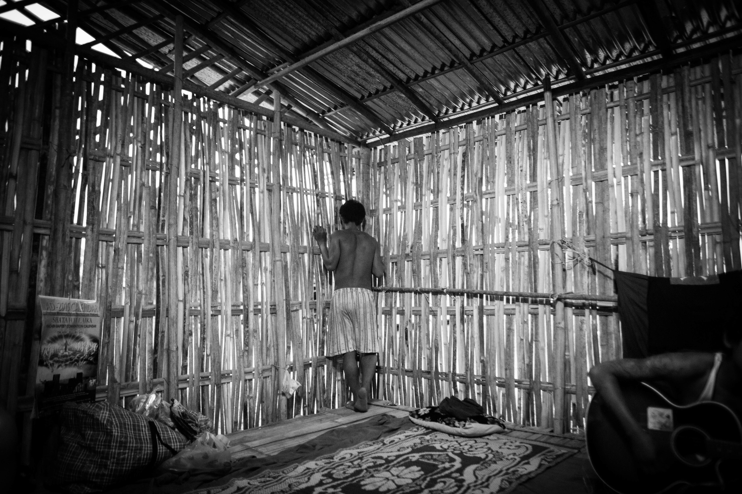 """Confined to a bamboo hut, the new students at the YCC rehab centertalk to the older students through spaces in bamboo slats of the """"prayer room."""""""
