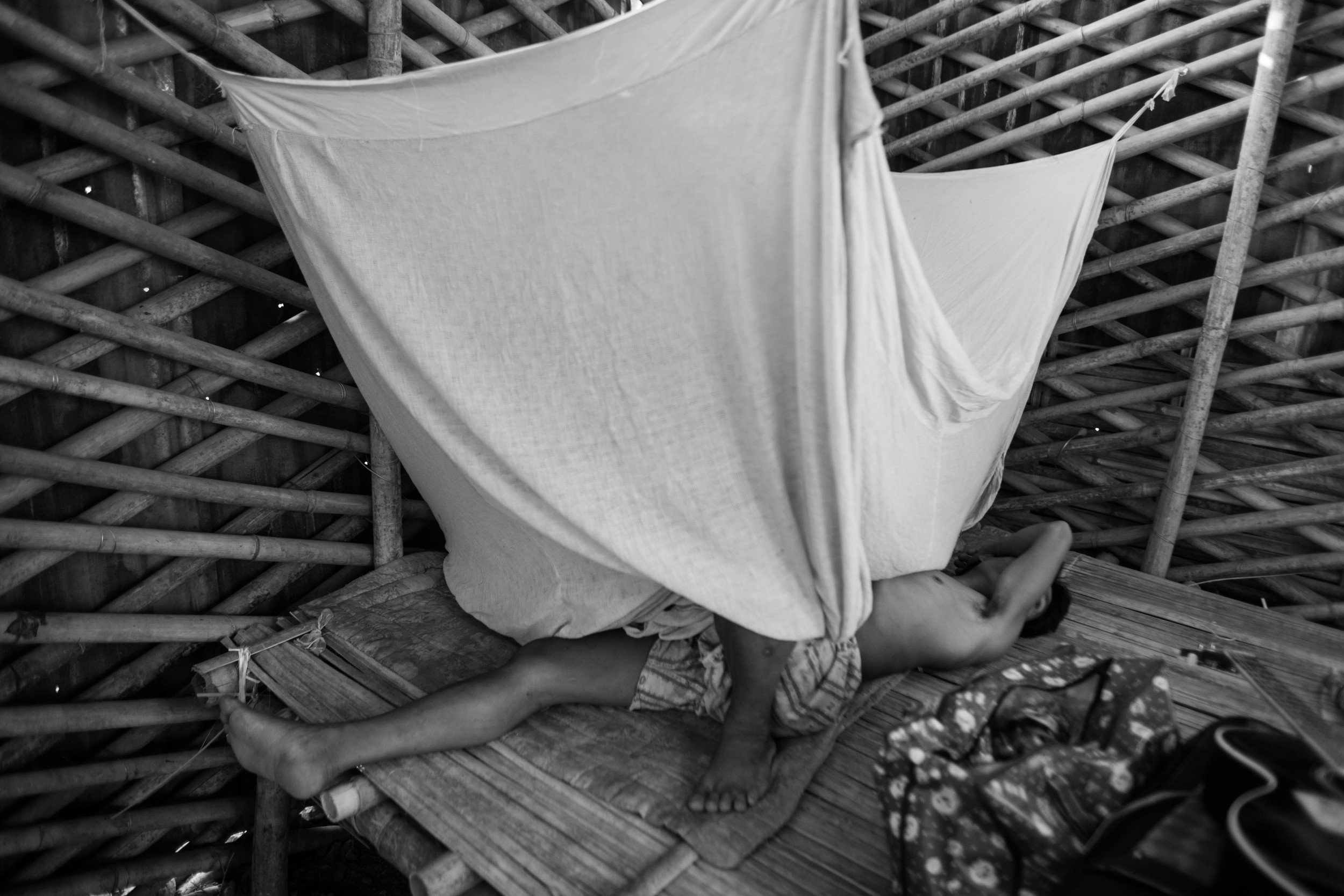 """""""Hkun Aung"""", an unofficial name he has given, rolls around in pain under his mosquito net."""