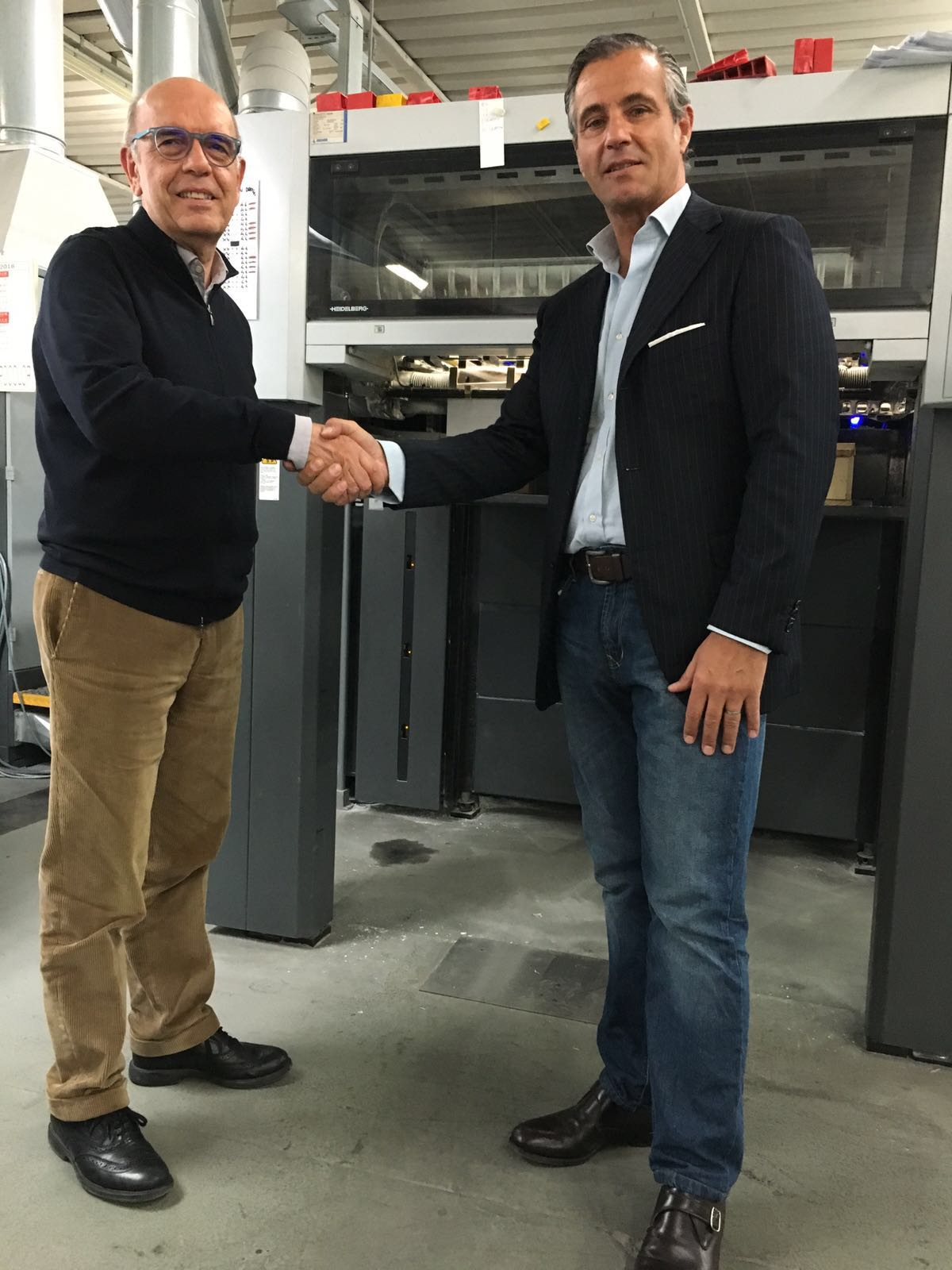 Dr. Roberto Conti shakes hands with AMS' Paolo Nascimbeni during the recent commissioning of their all-new AMS XP9 Series LED UV Printing System