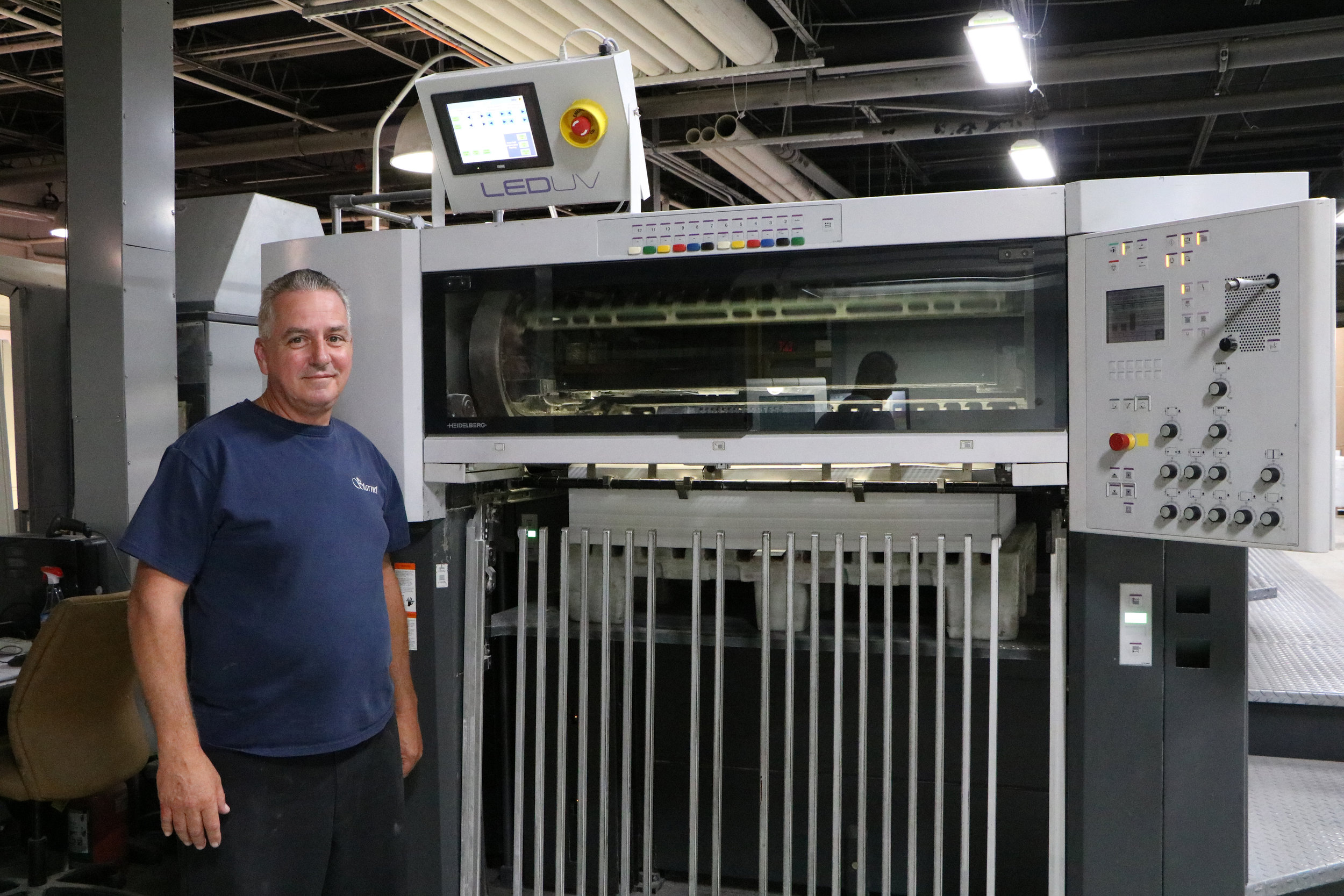 Veteran press operator John Cullen of Starnet Business Solutions pauses for a photo at the end of the company's Heidelberg Speedmaster press, which was retrofitted with an LED UV curing system from Air Motion Systems.