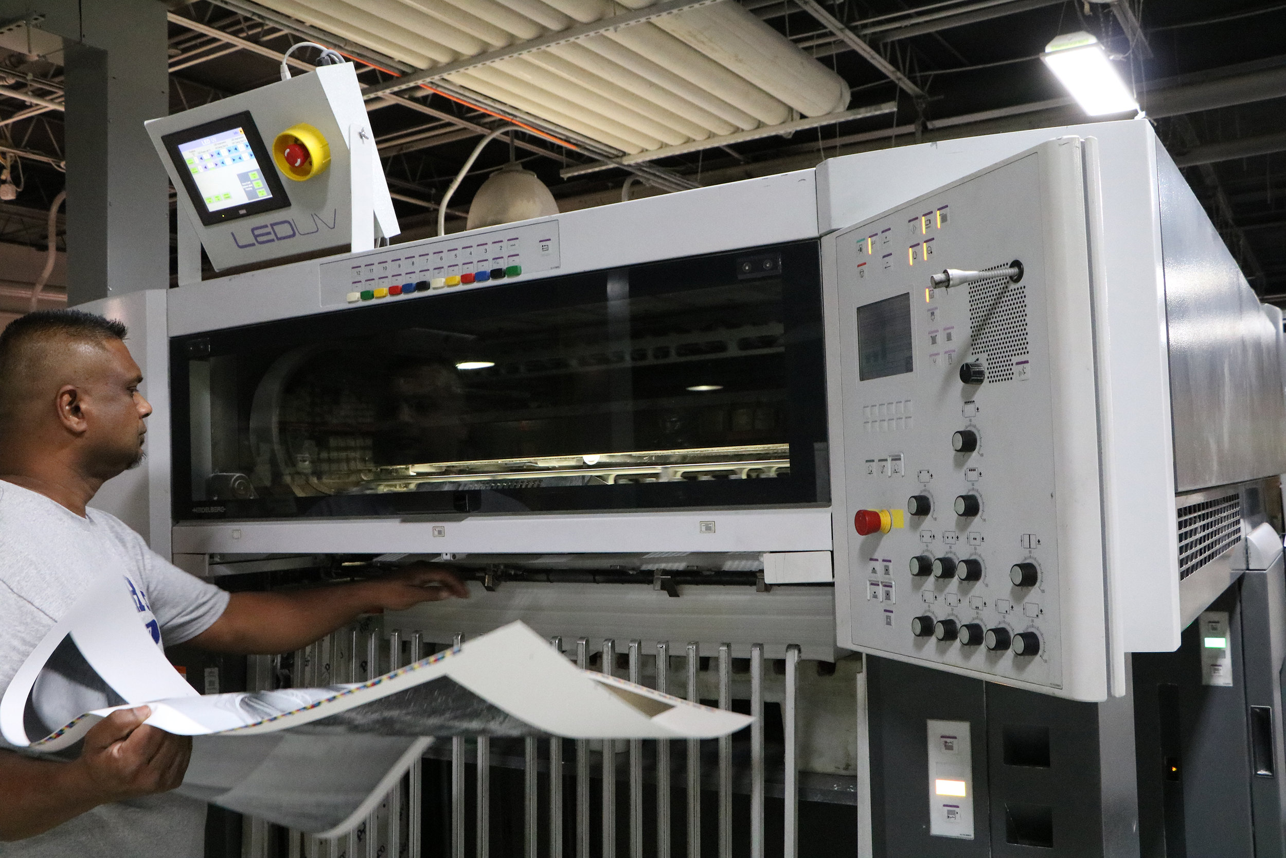 A Starnet press-team member pulls a dry sheet off of the press for checking.