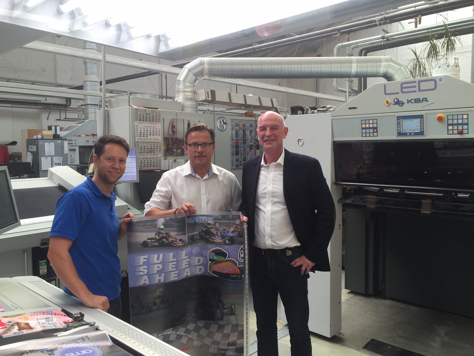 Flint Group's Richard Wilson (center) holds a poster printed with new LED-curable low-migration inks and coatings for in-mold labels while Königsdruck's Olaf König (right) and a press-team member join him. The new inks were cured using an XP9 LED module from AMS.