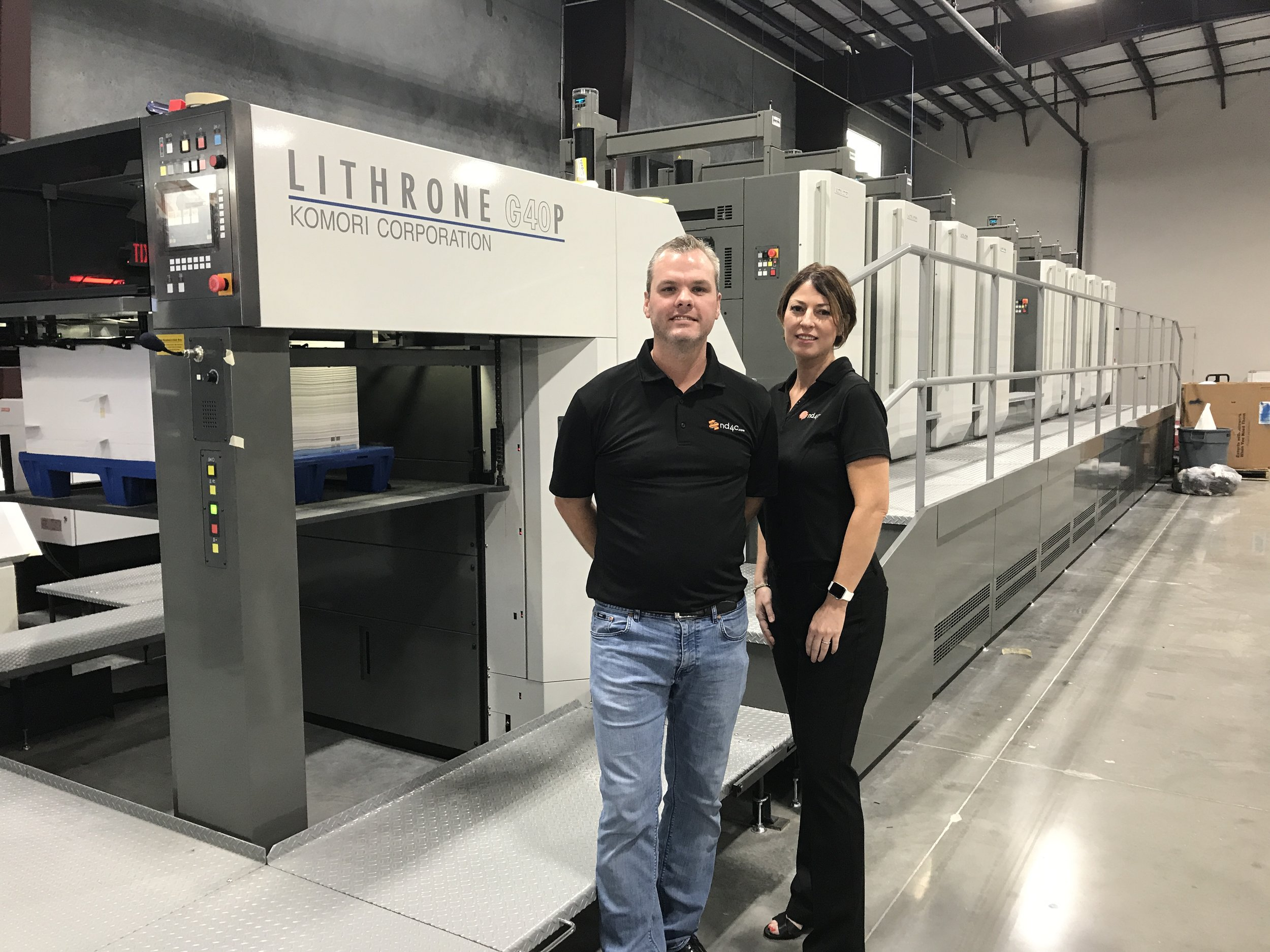 Shown here, Todd and Brandy Frost of Next Day Four Color pause in front of Komori press that is equipped with XO Series UV-LED technology from AMS Spectral UV - A Baldwin Technology Company.