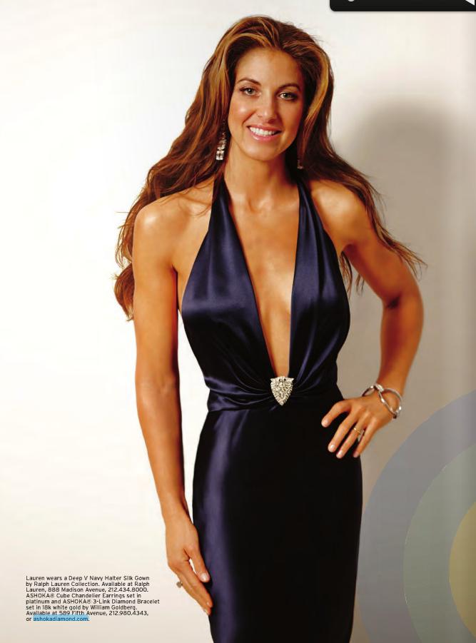 Lauren wears a Deep V Neck Halter Silk Gown by Ralph Lauren Collection. ASHOKA Cube Chandelier Earrings set in platinum and a ASHOKA 3-Link Diamond Bracelet set.