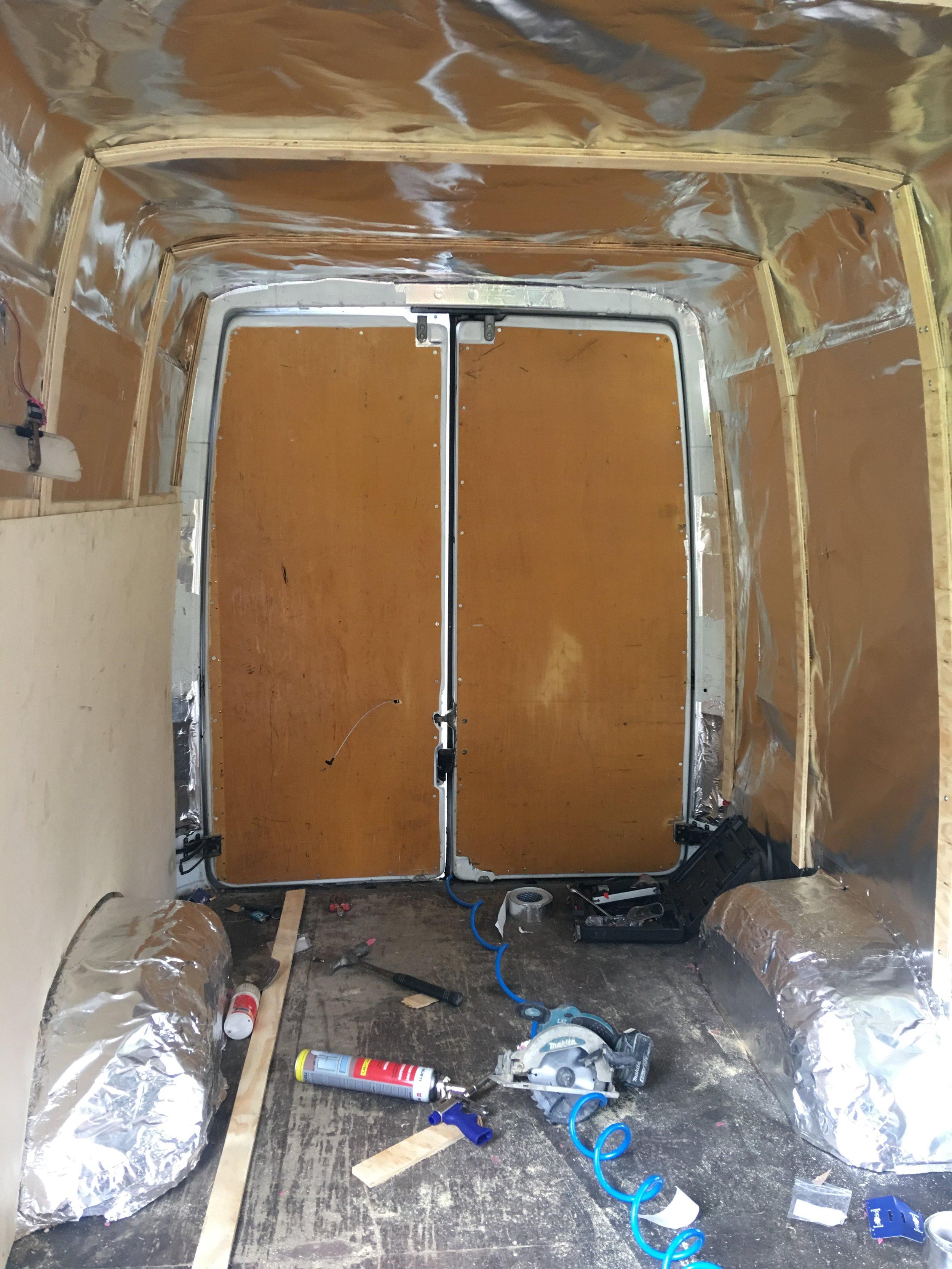 Seinien varsinainen verhoilu tehtiin koivuvanerista. Vanerilevyjen kiinnitystä varten tarvittiin tukirimat. Halusimme kattoon kulmien sijaan pyöreyttä. Vanerilevyt taivutettiin paikoilleen ja naulattiin kiinni tukirimoihin.  Taivutus onnistui hyvin. Katon rajassa, vasemmalla, näette suoraa kulmaa. Tuo kohta jäi myöhemmin rakennettujen hyllyjen taa piiloon. Näin säästettiin voimia,vaneria ja mikä tärkeintä,kaareva muoto ei syö säilytystilaa kaapin sisällä. Hienoin olisi ollut täysin kaareva katto, mutta tarvitaanhan retkiautoon toki myös retkivarusteet. Fiiliksen vuoksi päätimme jättääsängyn ylle avoimen tilan, jossa kaarevuus on kokonaista.
