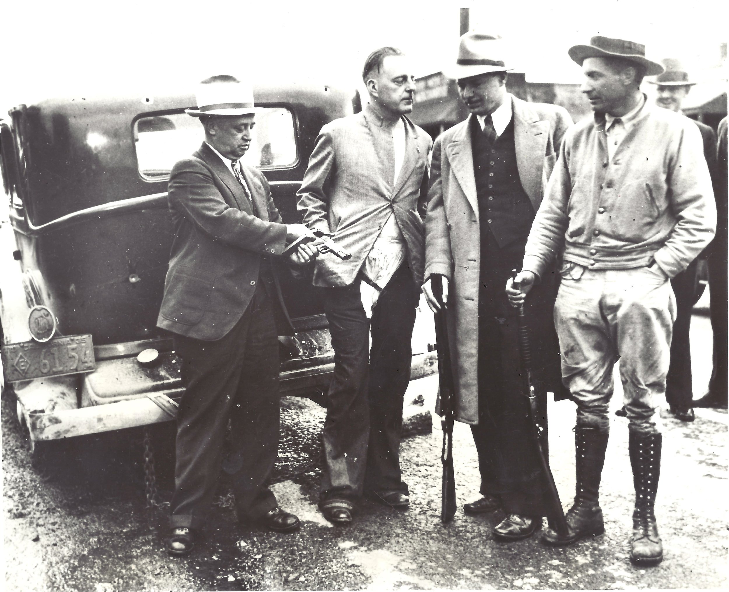The first photo shows (left to right) Marin Undersheriff Ed Blum, examining one of the convict's guns, Parole Board member Warren Atherton, who had been forced to change clothes with one of the convicts, Marin County District Attorney Al Bagshaw, holding the sawed-off shotgun he used to slay convict Rudolph Straight, and finally Constable John Bones, holding the rifle he used to shoot out the tire to the getaway car.  Note the bullet holes in the back of the warden's vehicle.