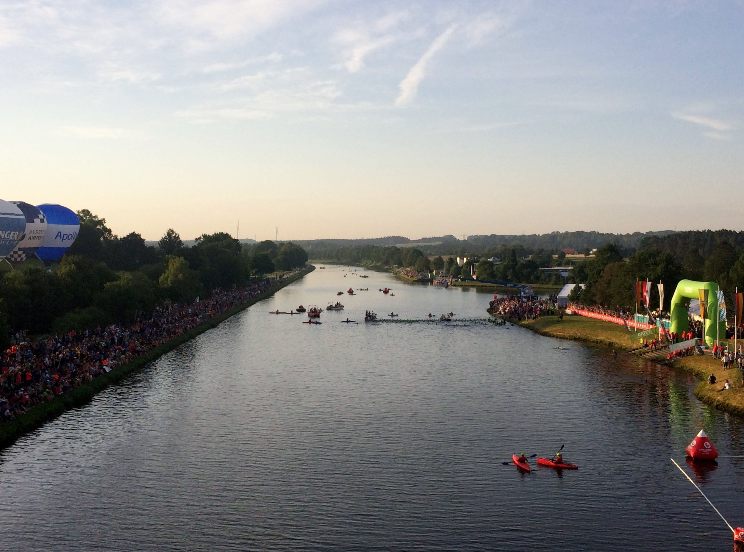 "The swim start at the canal is lined with spectators. Each ""wave"" will enter the water and be given a proper cannon shot to start their race."