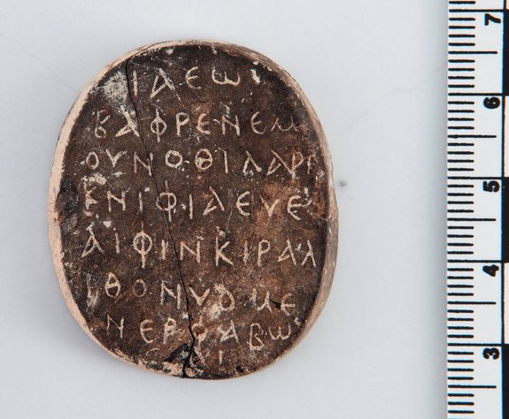 "For more information about this amulet, see http://www.livescience.com/49239-ancient-amulet-palindrome-inscription.html, where it was originally published.  The amulet is a palindrome.  It can be read forwards and backwards.  The message?  ""Iaeo is the bearer of the secret name, the lion of Re secure in his shrine."""