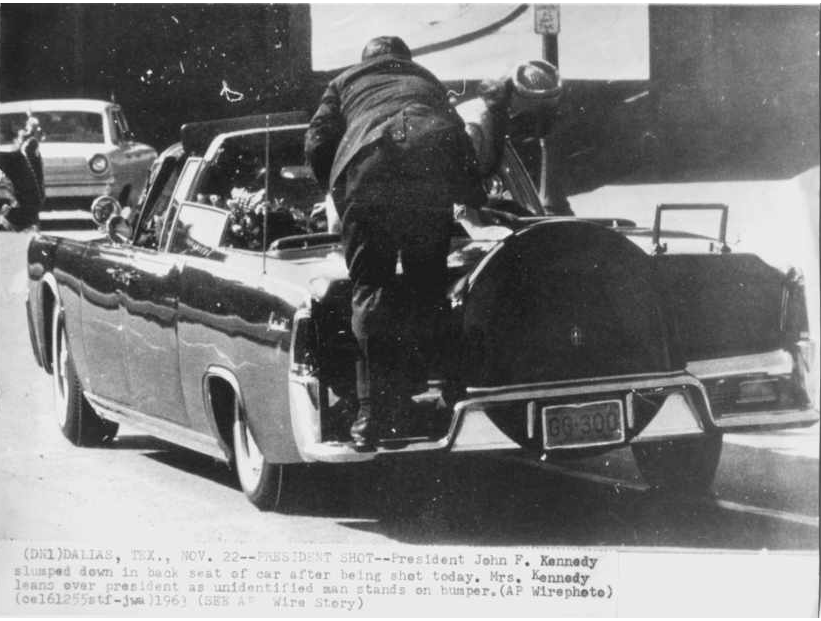 Photo 36- Clint Hill on the bumper of the Presidential vehicle.png
