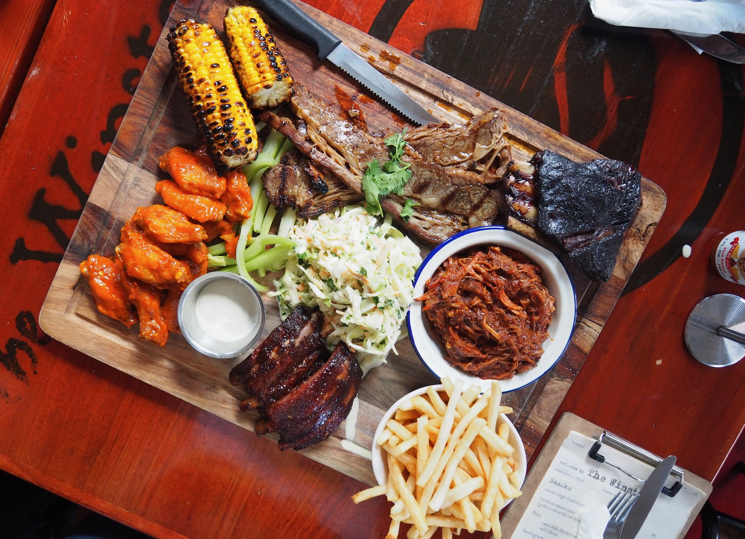 The BIG boy platter! Designed to share or to be a total glutton. Baby back ribs, buffalo wings, pulled pork, lamb ribs, maui brisket, fries, coleslaw and grilled corn. DANG!