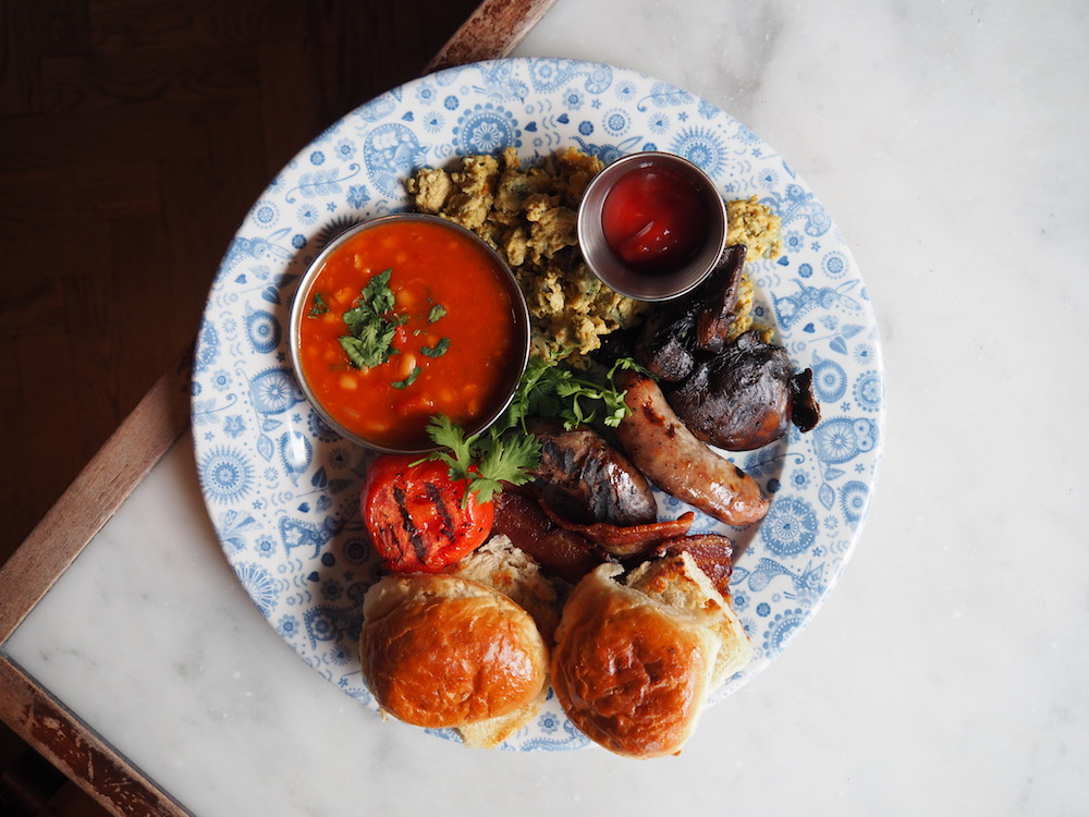 The Big Bombay | abundant Akuri, char-striped smoked streaky bacon from The Ginger Pig, peppery Shropshire pork sausages, masala baked beans, grilled field mushroom, grilled tomato and buttered, home-made buns.