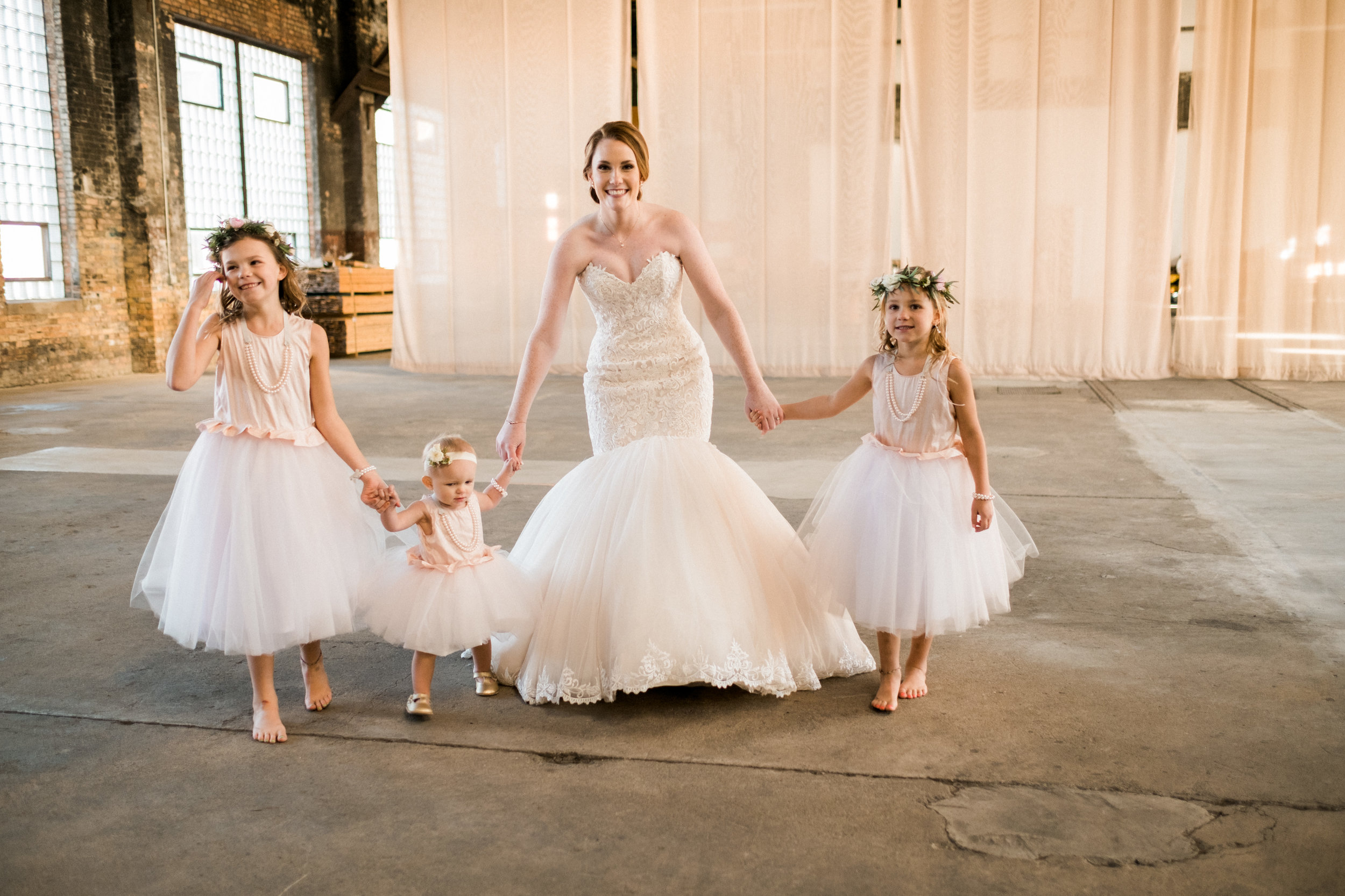 bride walking with the flower girls just before the wedding
