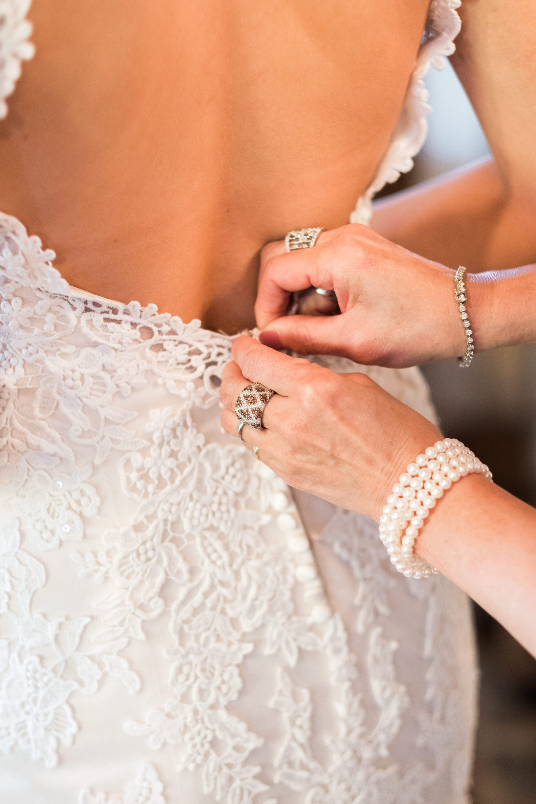 bride getting her dress buttoned