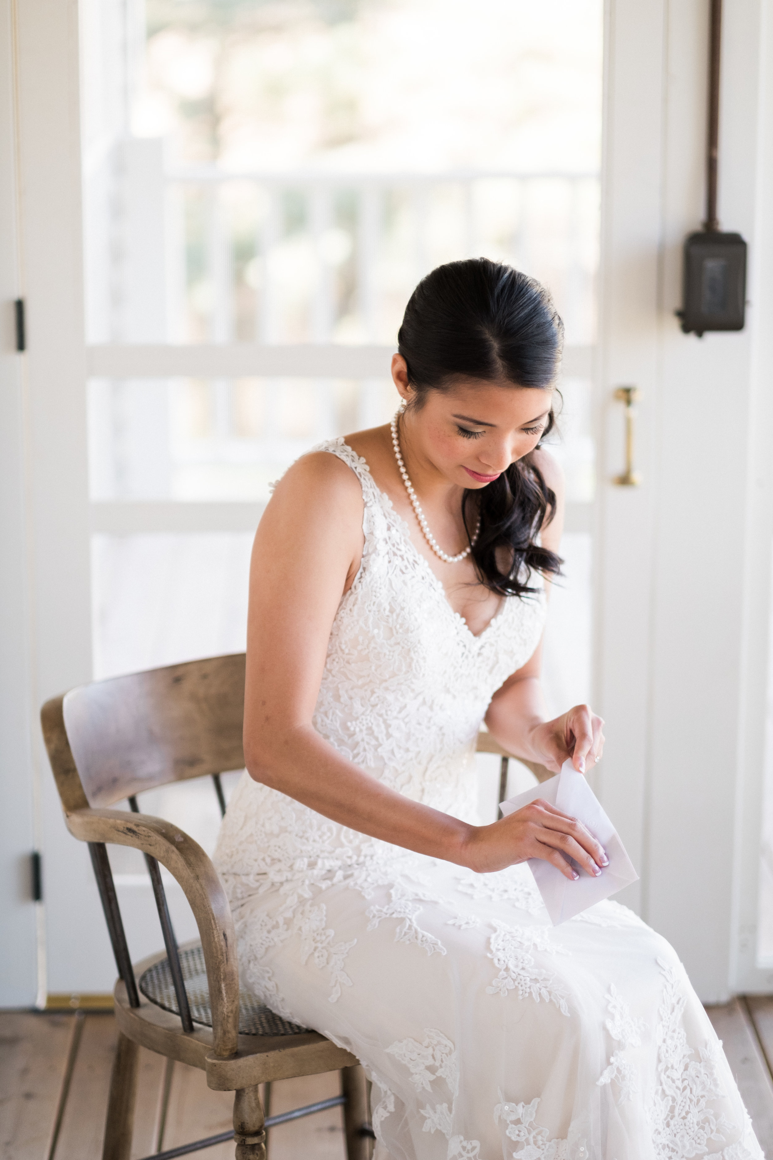 bride opening a love letter from her groom on her wedding day