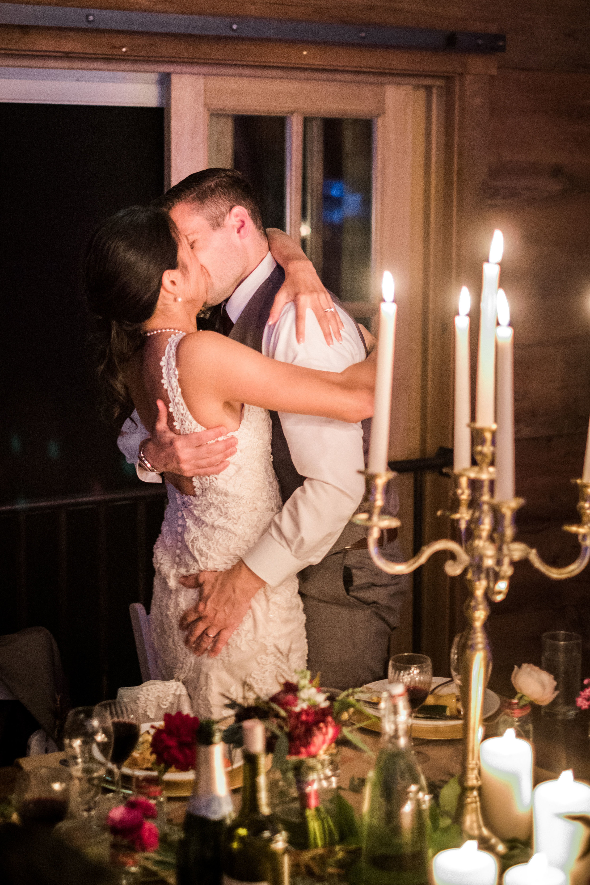 bride and groom kiss in their barn wedding reception