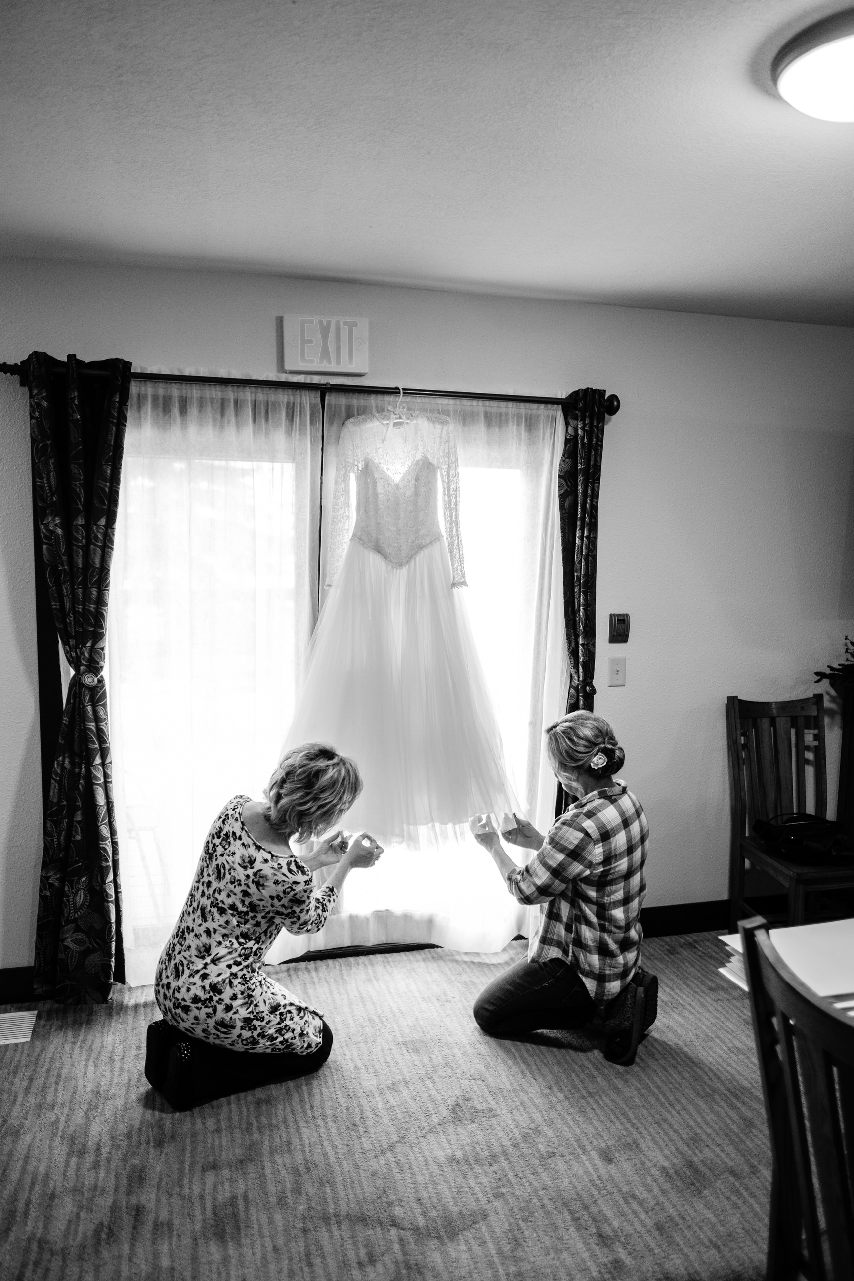 bride's mother and mother in law fixing her wedding dress