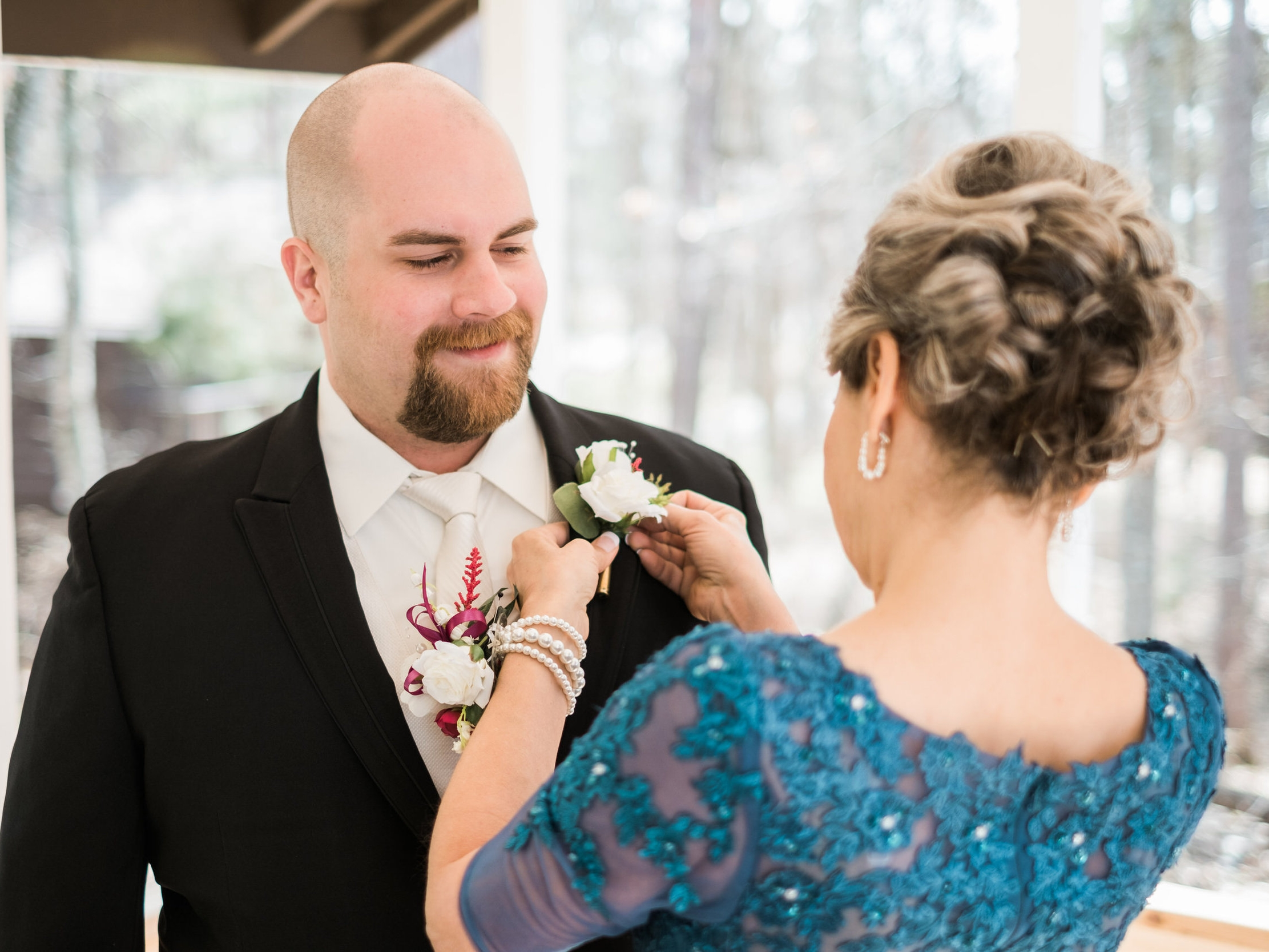 Groom receiving his boutinier from his mother for his Grand View Wedding