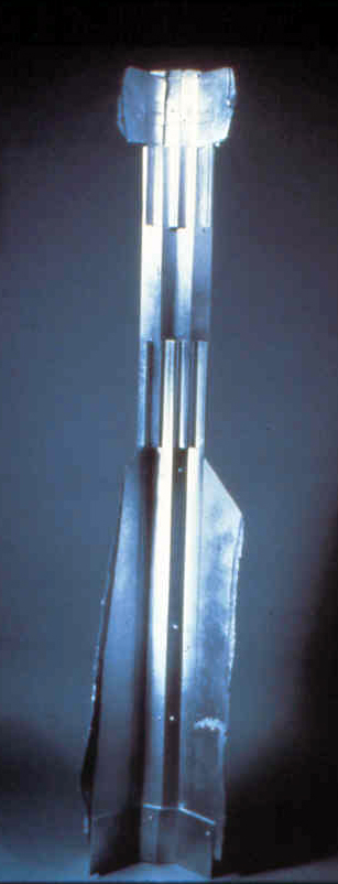 """Construction #4, nobody important   cardboard, aluminum spray paint  50"""" x 12"""" x7"""" , 1/15/1986  collection of the artist"""