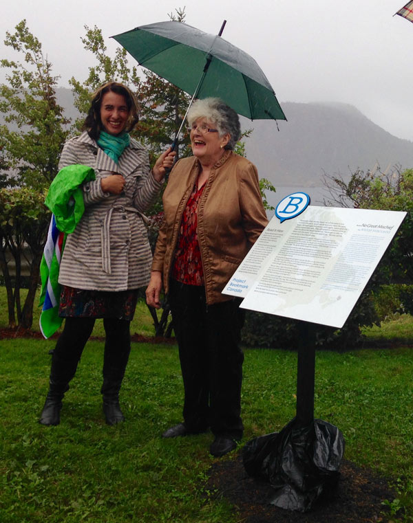 Project Bookmark Canada Founder Miranda Hill shelters Anita MacLeod at the unveiling. Photo Credit: Weldon Bona.