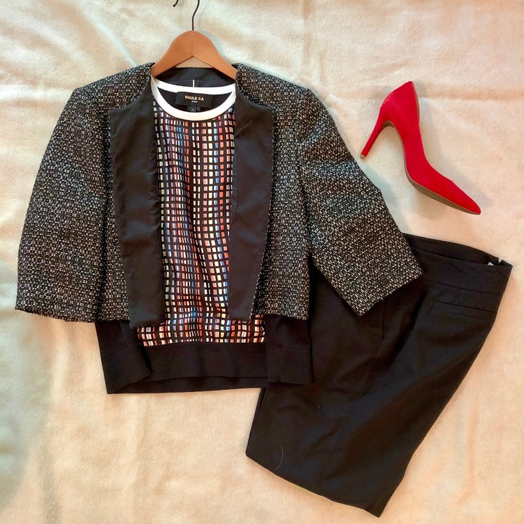 Yes, you can have fun at work by pairing a black and white textured jacket with a multicolored geometric print top. Black pants ground the look, and you can never go wrong with a pop color heel.