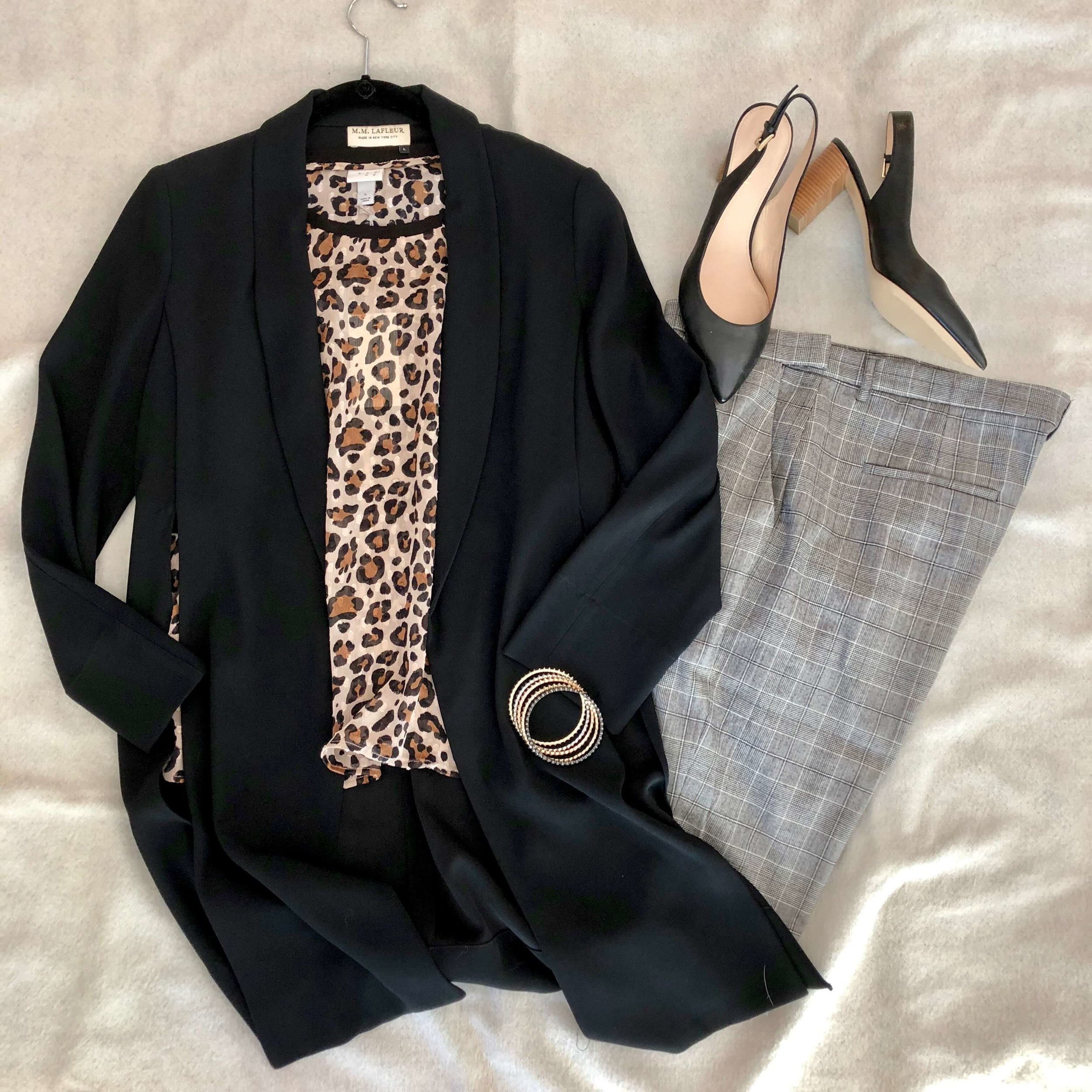 A black blazer and plaid pants may not feel specifically feminine, but the juxtaposition of leopard print shifts it to a much more stylish look.