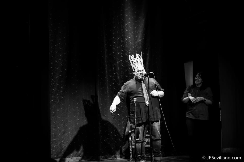 Matt Hill wearing hand-cut paper mask for raffle, Mabel Bermejo running raffle