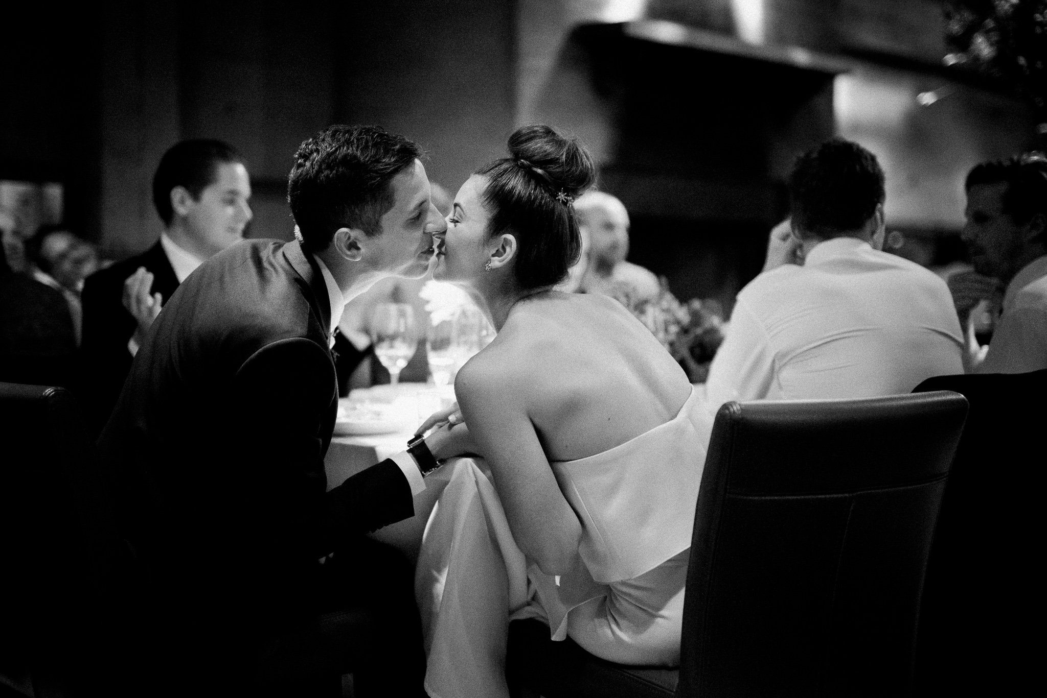 Bride and groom kissing at reception table at Foreign Cinema, San Francisco